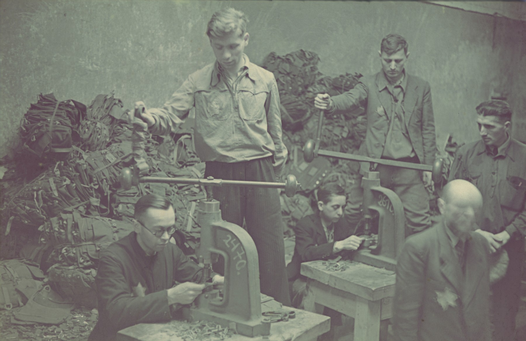 "Workers fashion metal fasteners in the saddle making workshop of the Lodz ghetto.  Original German caption: ""Getto-Litzmannstadt, Sattlerei"" (saddlery), #189."