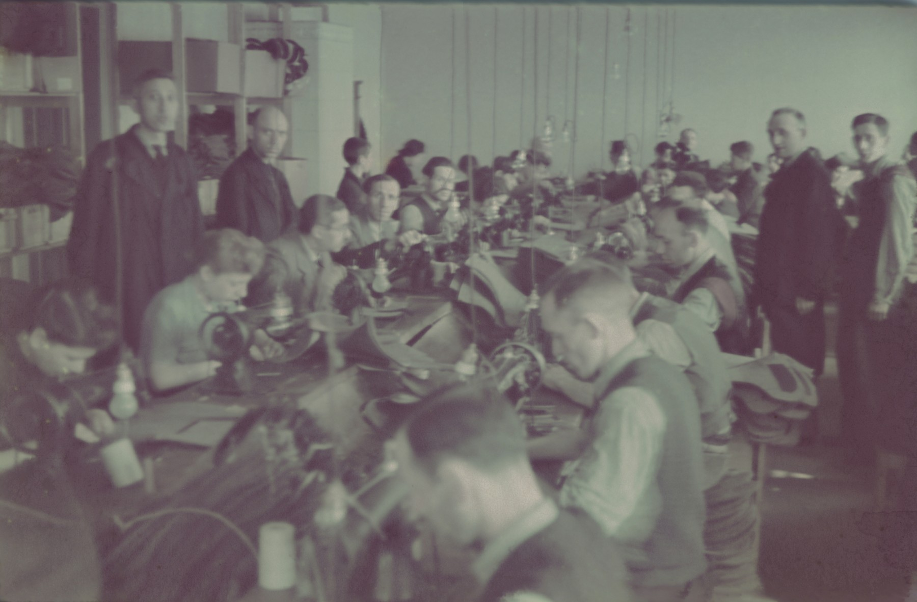 """Workers operate sewing machines in the saddle-making workshop of the Lodz ghetto.  Original German caption: """"Litzmannstadt Getto, Sattlerei"""" (saddlery)."""