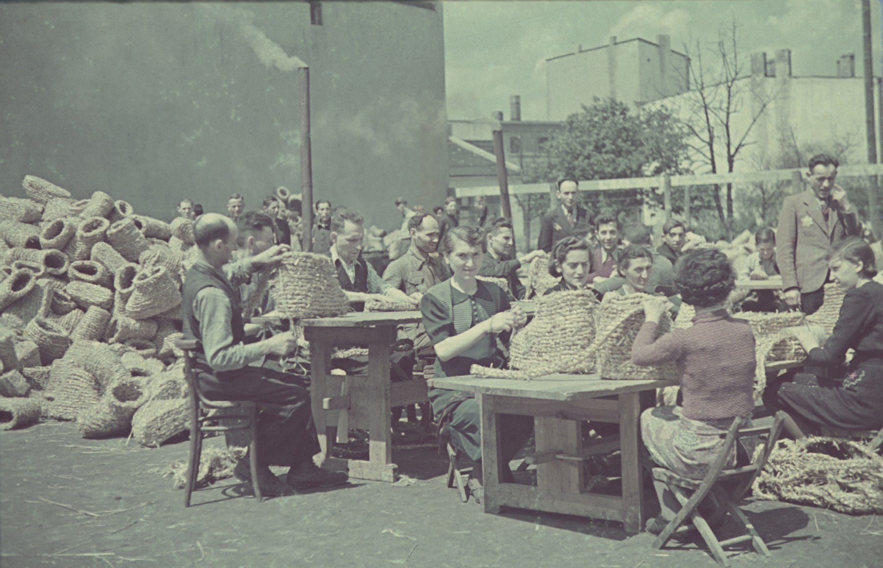 """Workers roll up coils of straw in the straw shoe factory of the Lodz ghetto.  Original German caption: """"Getto-Litzmannstadt, Strohschufabrik"""" (straw shoe factory), #207."""