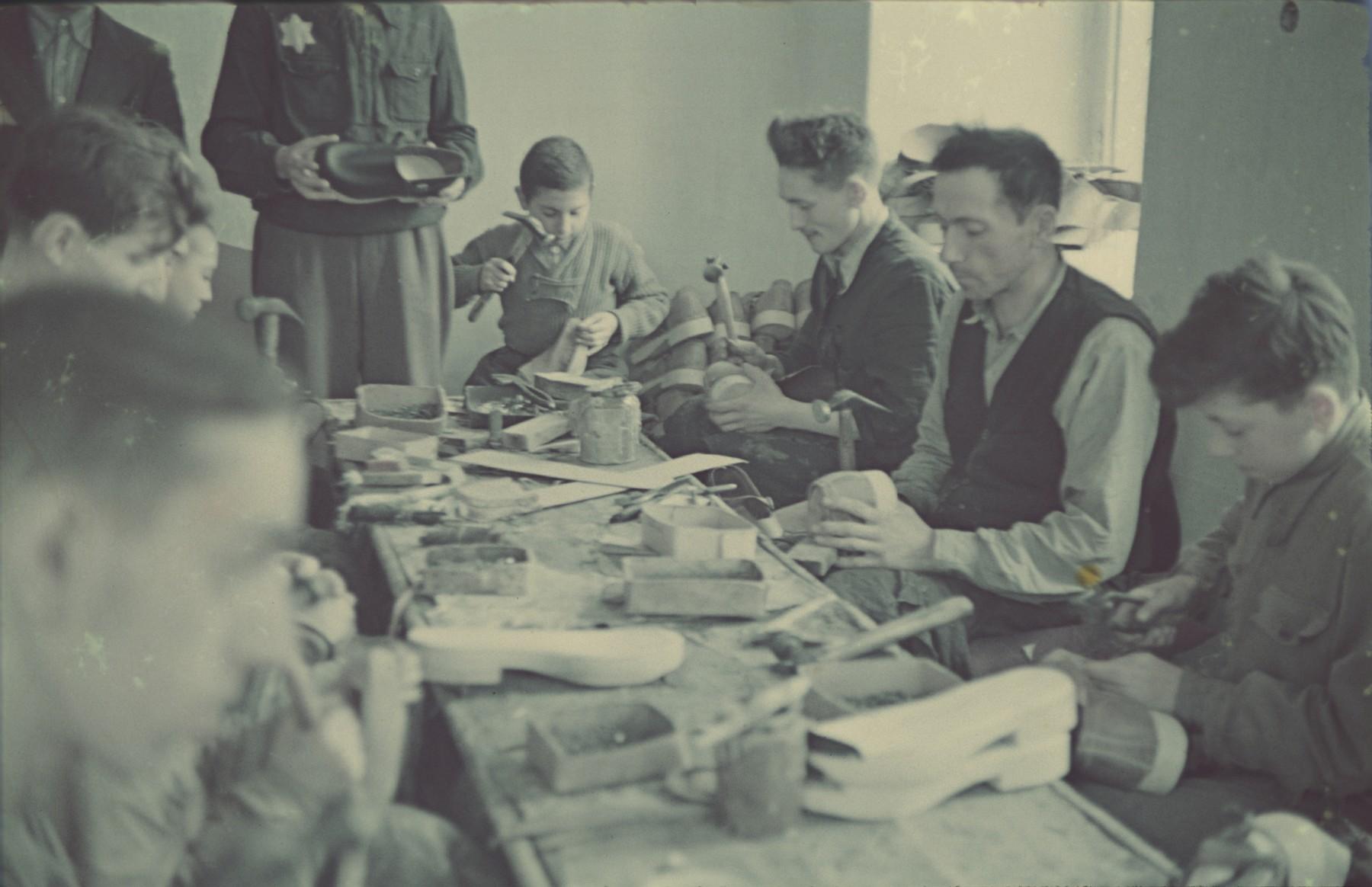 "Workers manufacture wooden shoes in the Lodz ghetto.  Original German caption: ""Litzmannstadt-Geto, Holtzschufabrik"" (wooden shoe factory), #19."