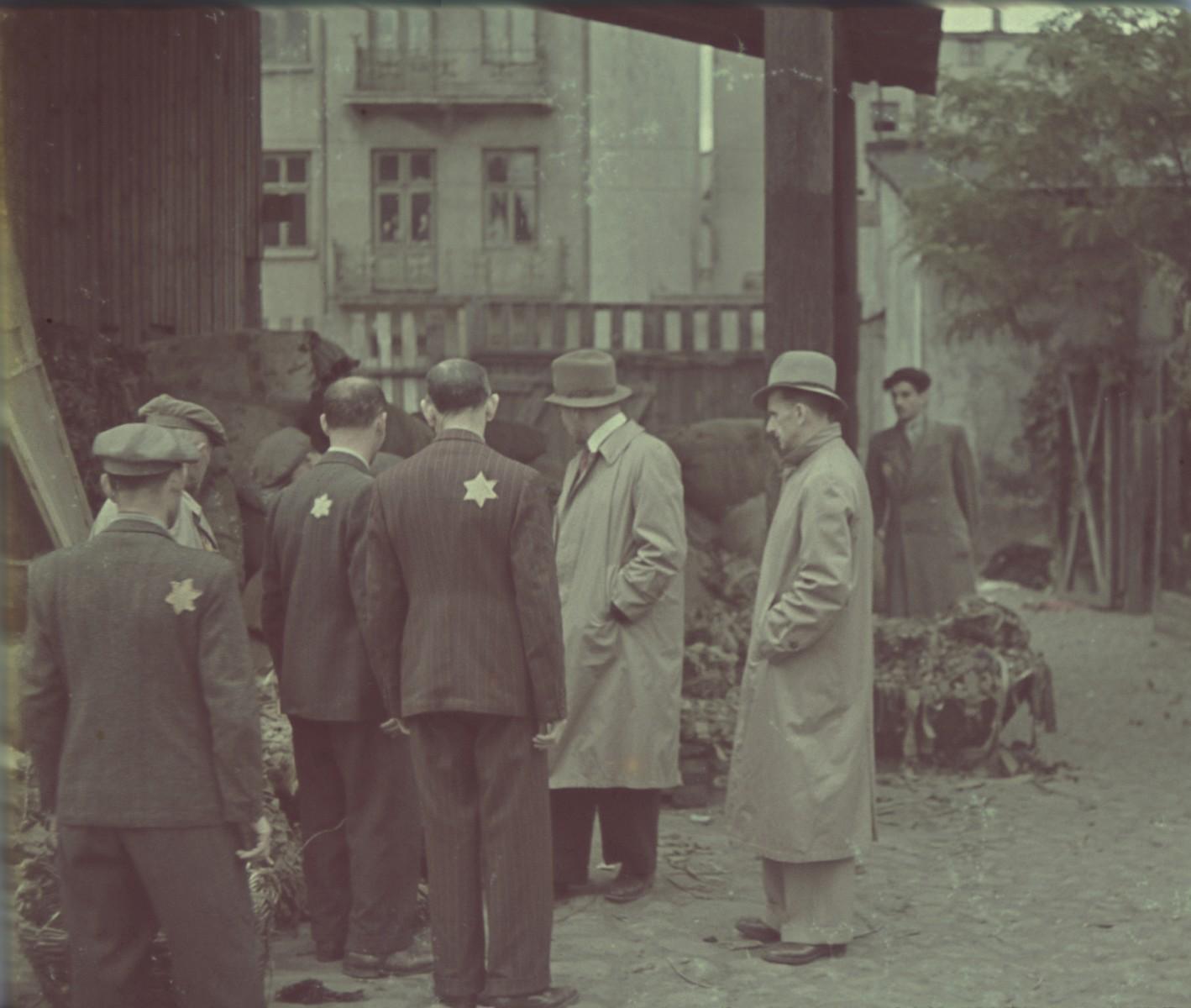 "Workers gather around a pile of material in the belt and strap depot.  Original German caption: ""Litzmannstadt-Geto, Gurtenlager"" (belt warehouse), #24."