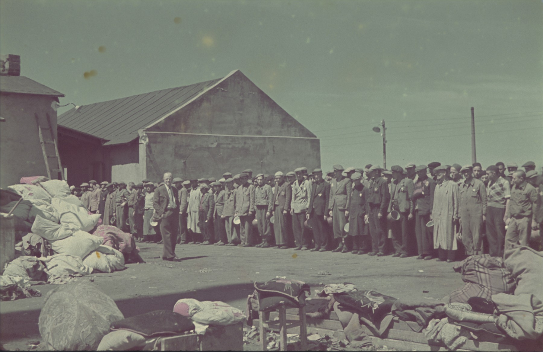 "Jewish men wait for their lunch rations in the Pabianice labor camp/storage facility.  Original German caption: ""Pabianice, Mittagessen"" (lunch). #36."