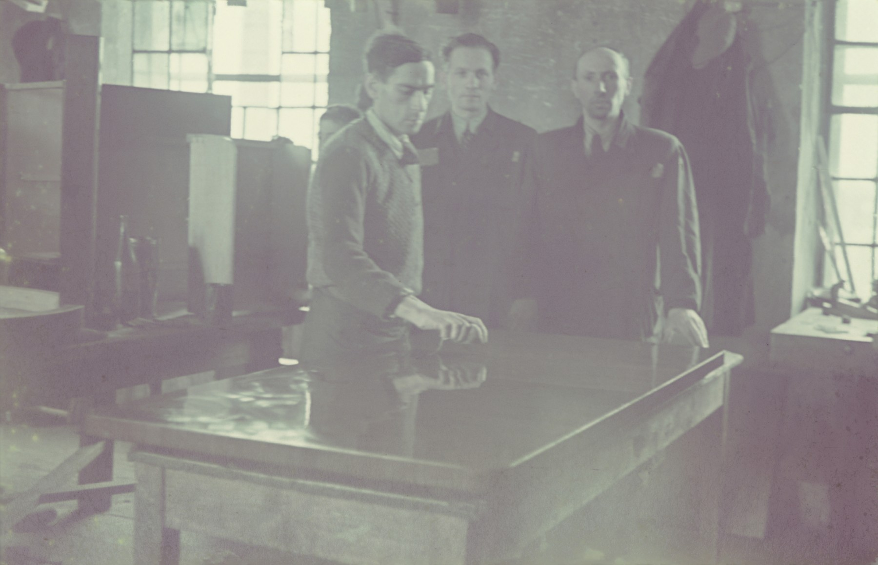 """Three men examine the finish of a table in the furniture factory of the Lodz ghetto.  Original German caption: """"Getto-Litzmannstqadt, Moebelfabrik"""" (furniture factory), 1942, #12."""
