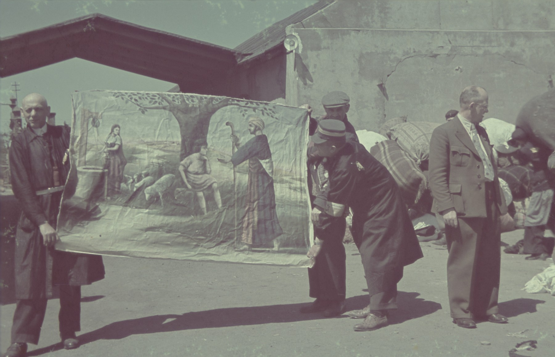"""Jewish laborers display a confiscated work of art that was brought to the Pabianice labor camp/storage facility.  Original German caption: """"Pabianice, Juedische Kunst"""" (Jewish art), #33."""
