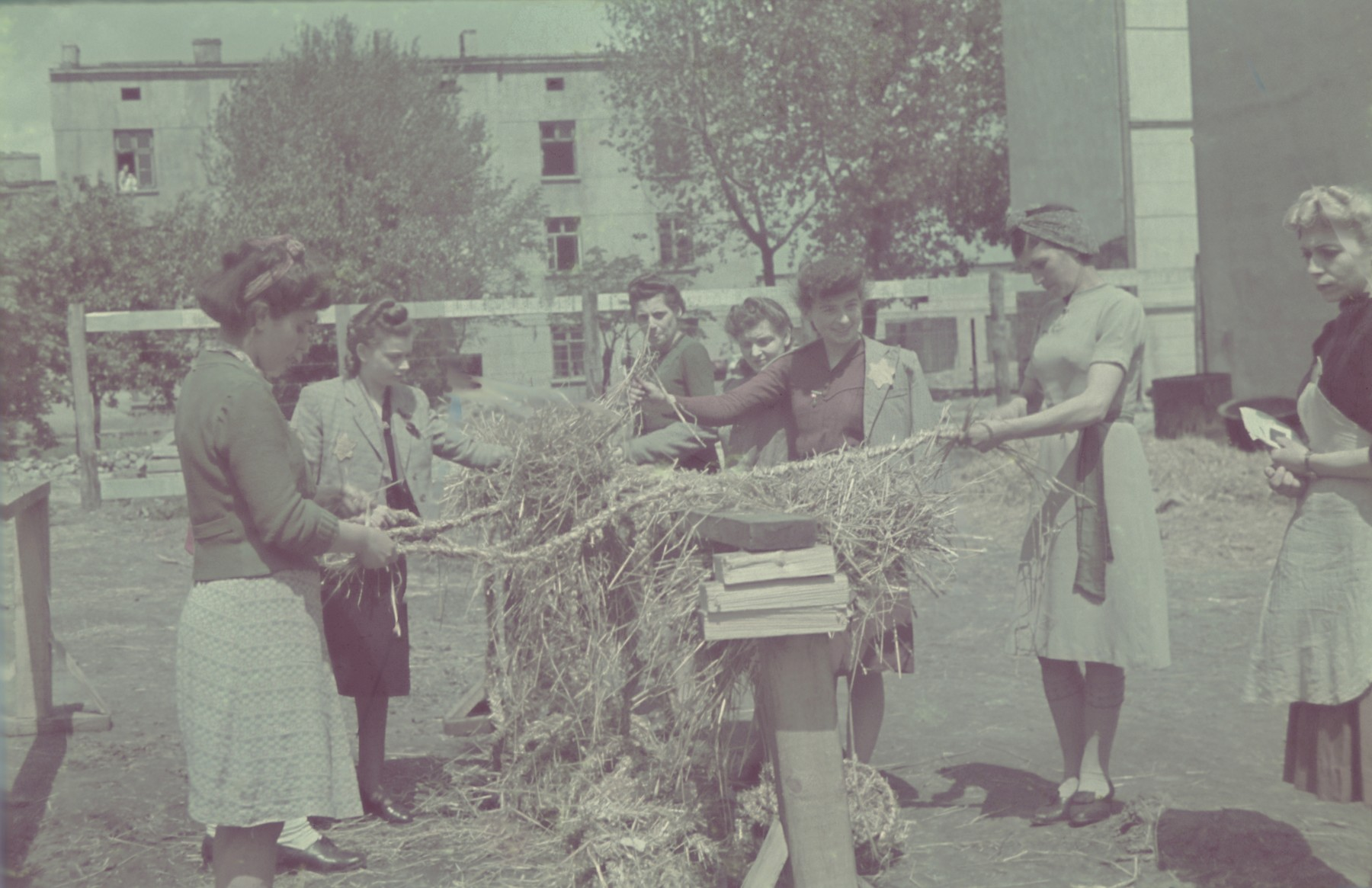 "Women twist straw into rope in the courtyard of the straw shoe factory in the Lodz ghetto.  Original German caption: ""Getto-Litzmannstadt, Strohschuhfabrik"" (straw-shoe factory), #208."