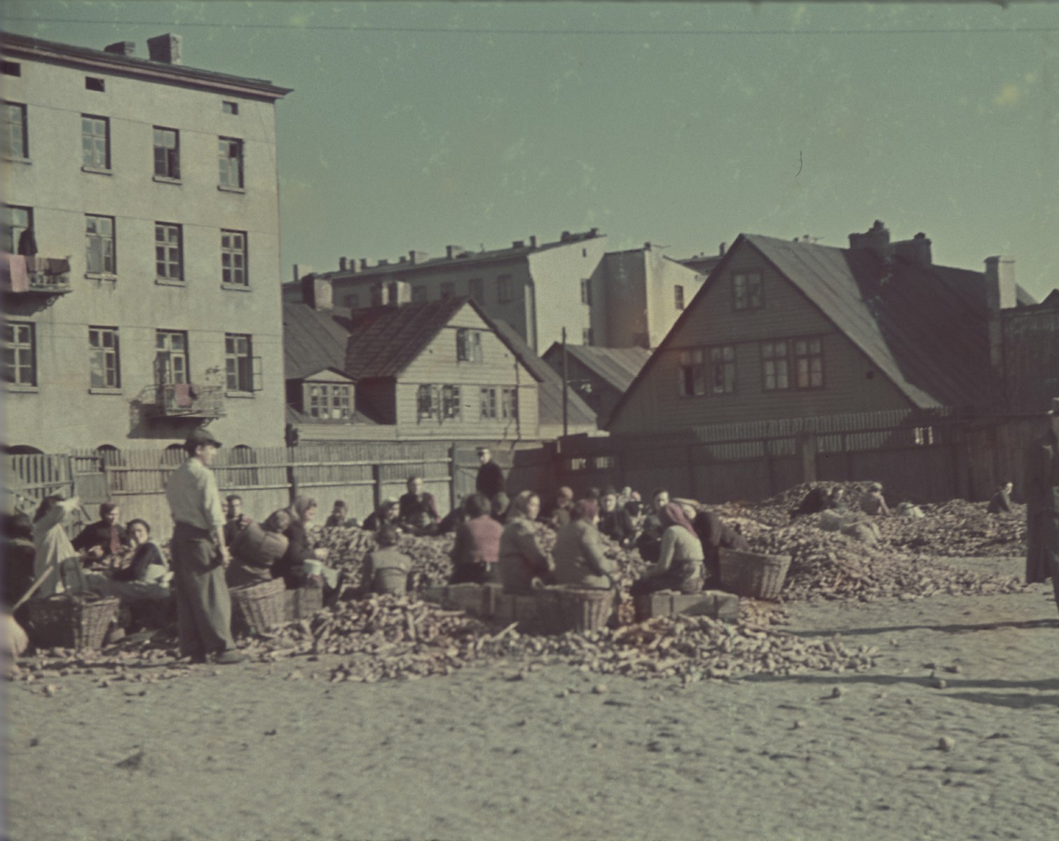 "Women sit on crates in a large open square and sort out vegetables.  Original German caption: ""Lagerplatz"" (camp square) #143."