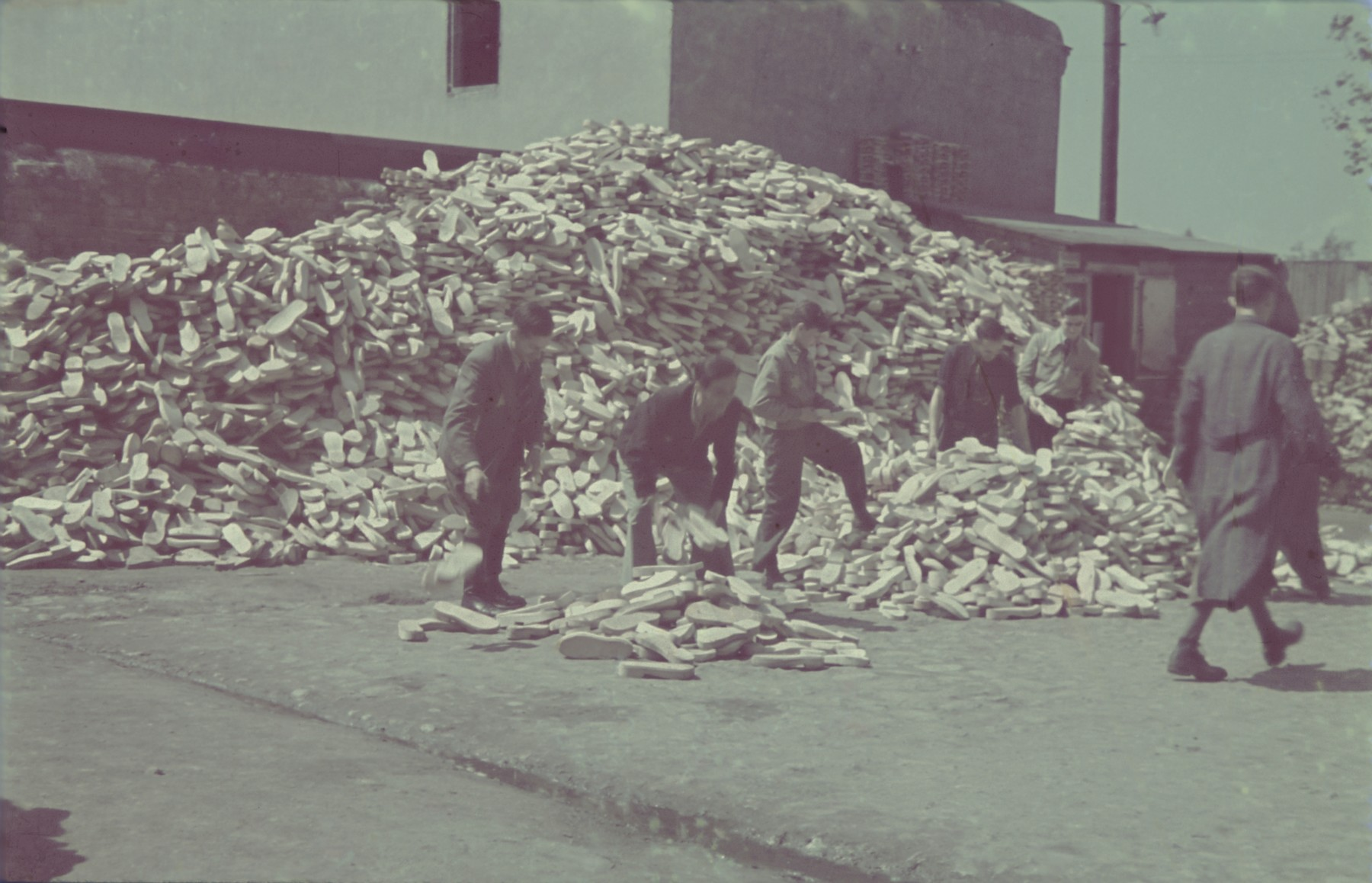 """Workers stack wooden soles in a large pile in the Lodz ghetto wooden shoe factory.  Original German caption: """"Litzmannstadt-Getto, Holzshcufabrik"""" (wooden shoe factory)."""