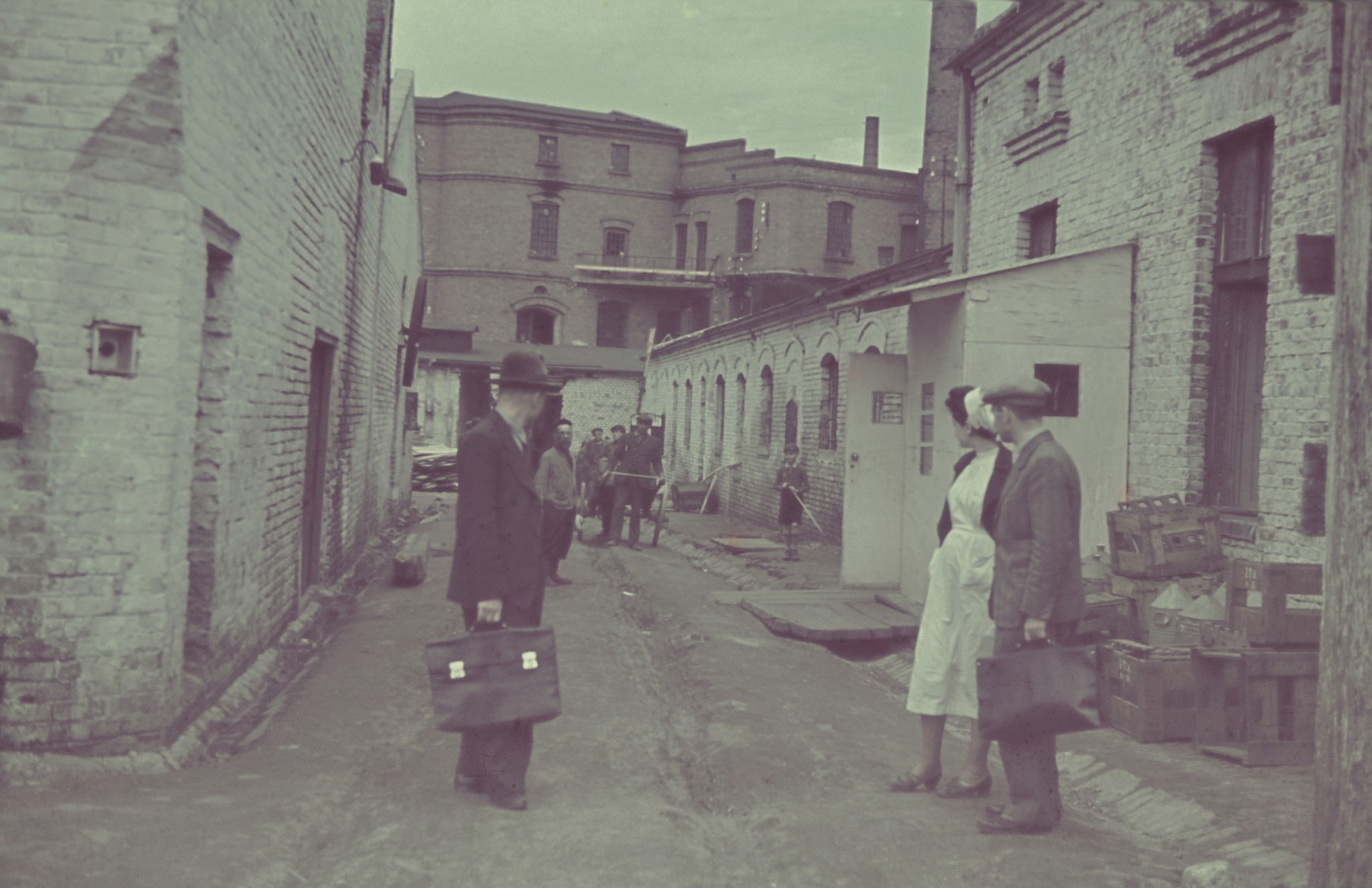 """Two men and a female nurse converse outside the furniture factory in the Lodz ghetto.  Original German caption: """" Getto-Litzmannstadt, Moebelfabrik"""" (furniture factory), 1942, #275.  (number 169 is crossed out)"""