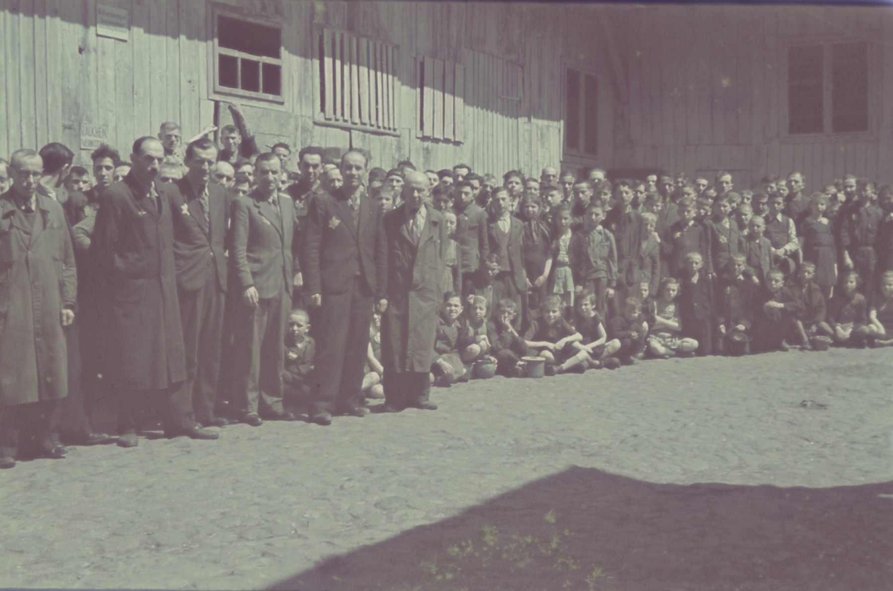 "Group portrait of personnel, including many children, of the furniture factory in the Lodz ghetto.  Original German caption: ""Getto Litzmannschaft, Gefolgschaft der  Moebelfabrik"" (personnel of the furniture factory), #177."