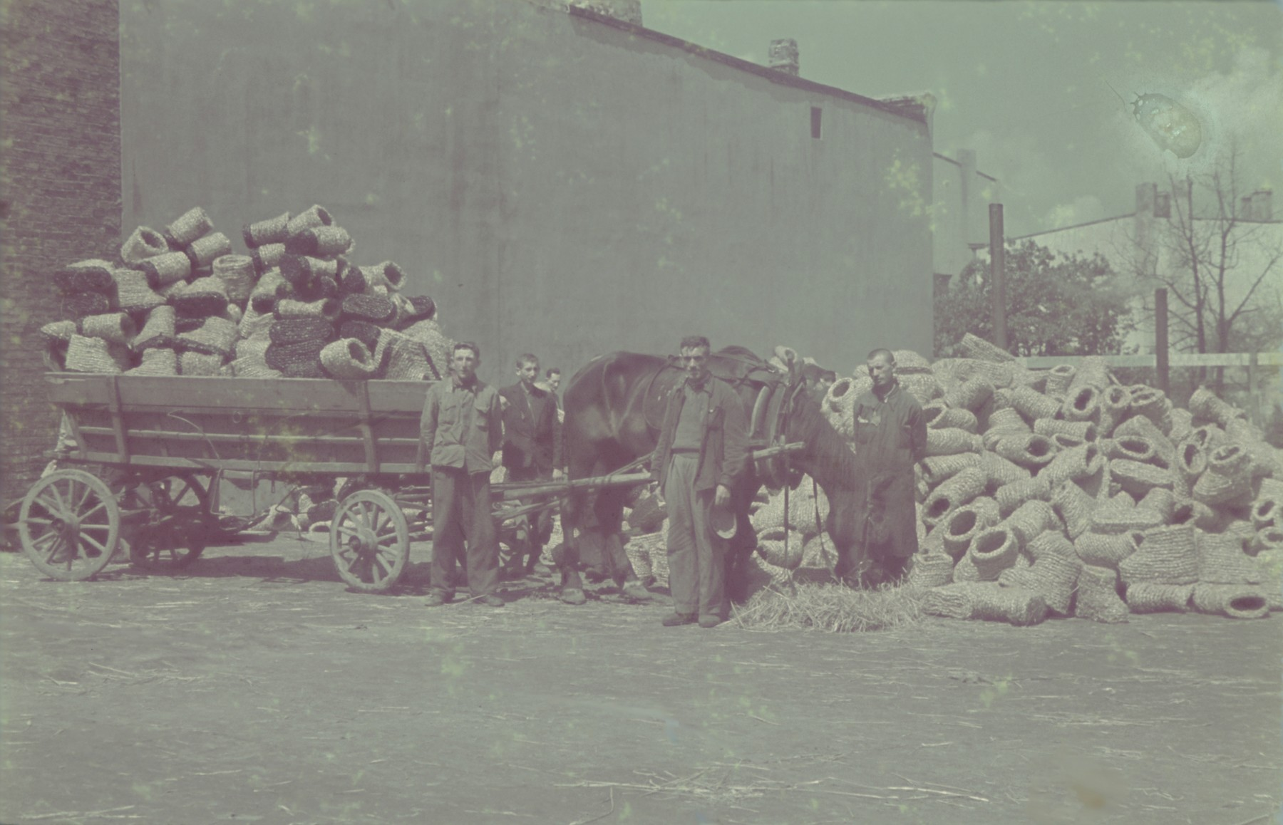 "Workers pile coils of straw onto a horse-drawn cart outside the factory for straw shoes in the Lodz ghetto.  Original German caption: ""Getto Litzmannstadt, Strohschuhfabrik"" (straw shoe factory), #205."