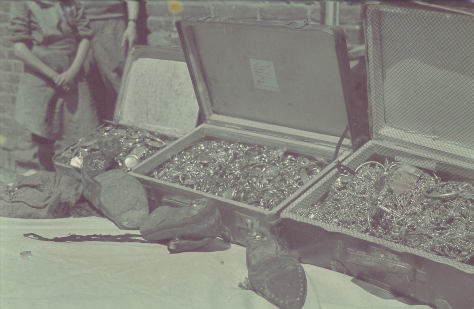 """A display of confiscated valuables, some buried in the heels of shoes, collected and sorted in the Pabianice labor camp/storage facility.  Original German caption: """"Pabianice, Versteckte Werte"""" (hidden valuables), #31."""