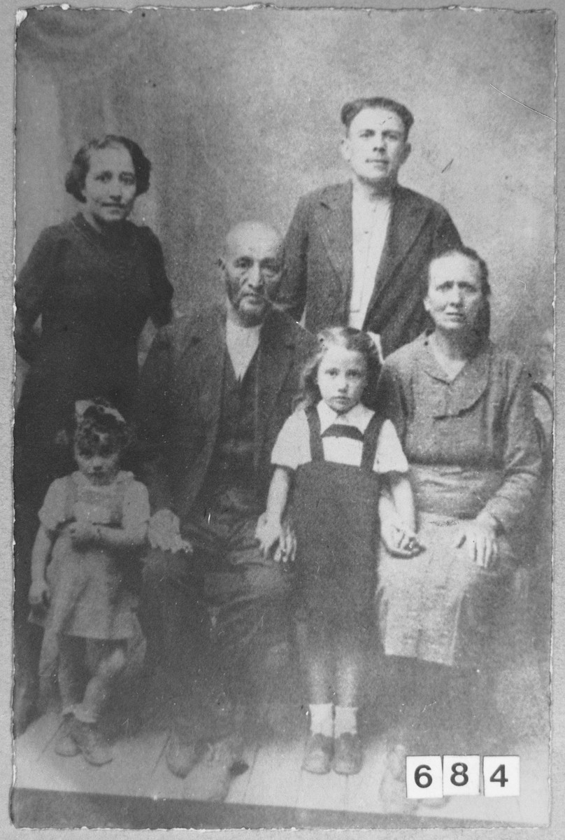 Portrait of Menachem Todelano, his wife, Miram, Mordechai Massot and his wife Luna.  Menachem was a second-hand dealer.  Menachem and Miriam lived at Bistritska 9 in Bitola.  Mordechai was a rag dealer.  Luna was a laundress and she lived at Sinagogina 12 in Bitola.  Also pictured are two unidentified children.