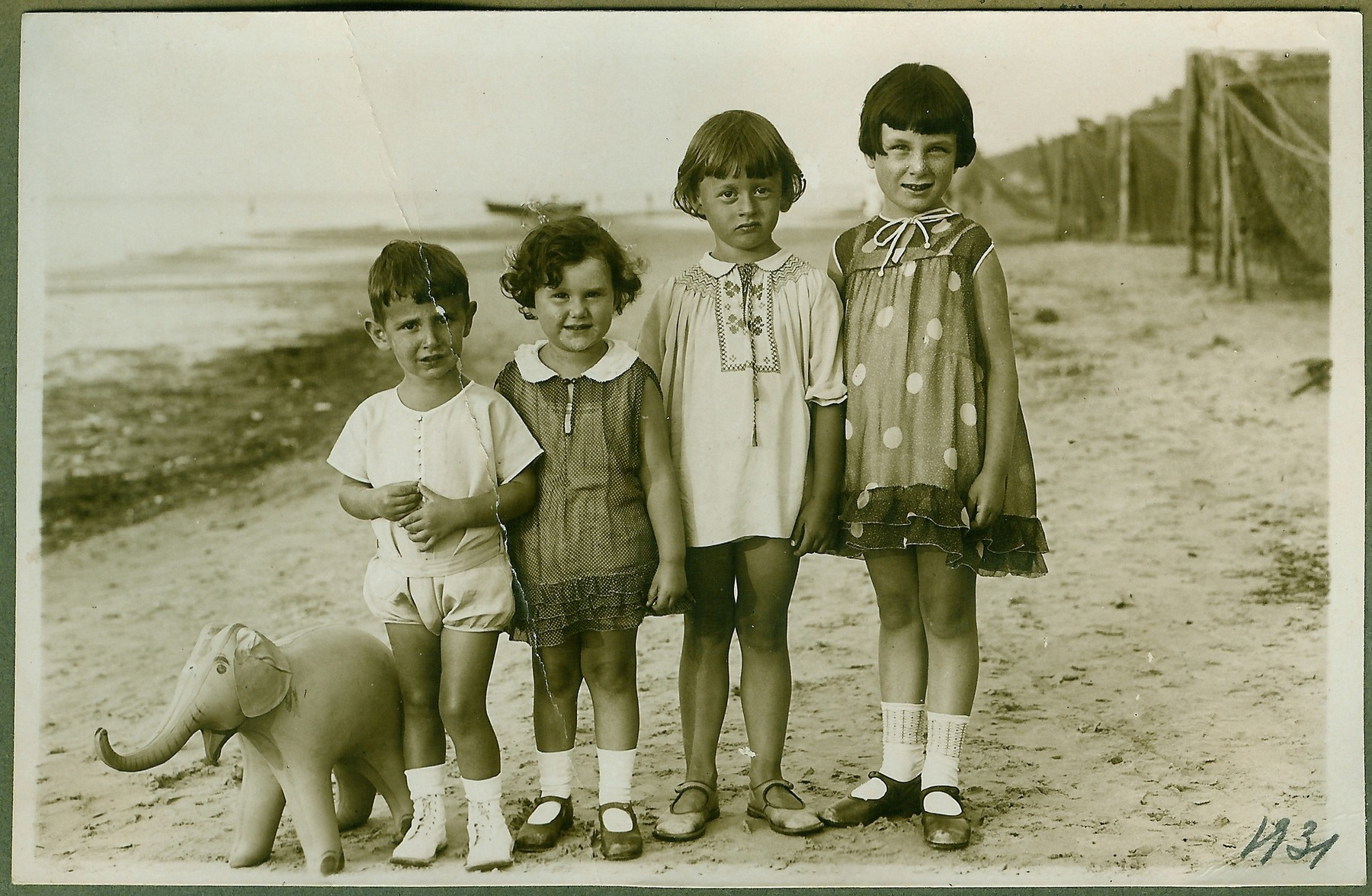 Four young children stand in a row next to a toy elephant on the Latvian shore.  Dmitri Kopelman is pictured on the far left.
