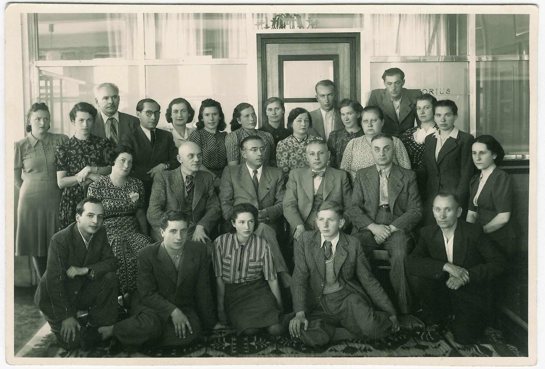 Group portrait of the staff of the Lietuvos Lloydas insurance company.  Among those pictured are Dmitri Gelpern (first row, left), Aleksandras Valaitis (middle row, second from left), Moisei Kopelman (middle row, third from left), Mikhail Fratkin (middle row, fourth from left), and Olga Zirickiene (back row, between Kopelman and Fratkin).  Dmitri Gelpern later became a leader of the Communist underground in the ghetto; Moisei Kopelman became ghetto chief of police, and Aleksandras Valaitis became a rescuer.
