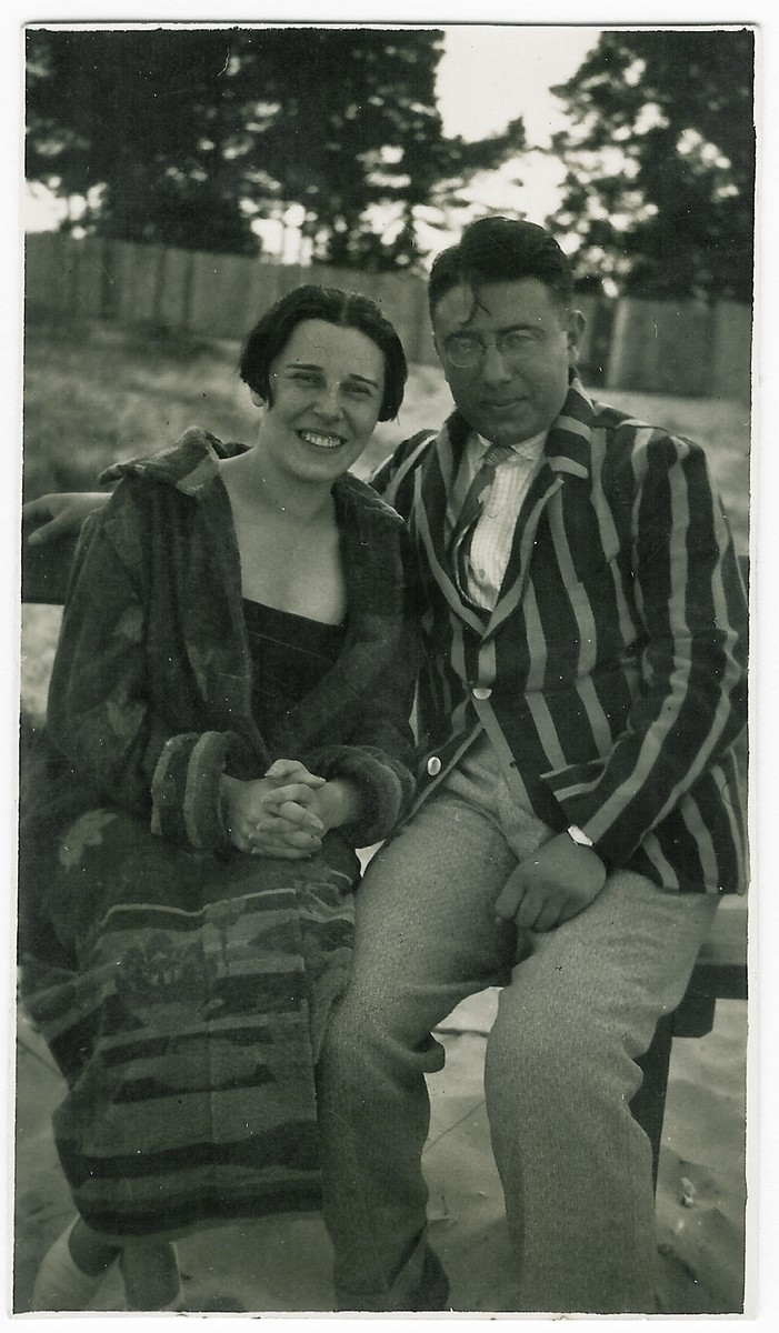 A young Jewish couple poses together on a park bench.  Pictured are Moisei and Eugenia Kopelman.