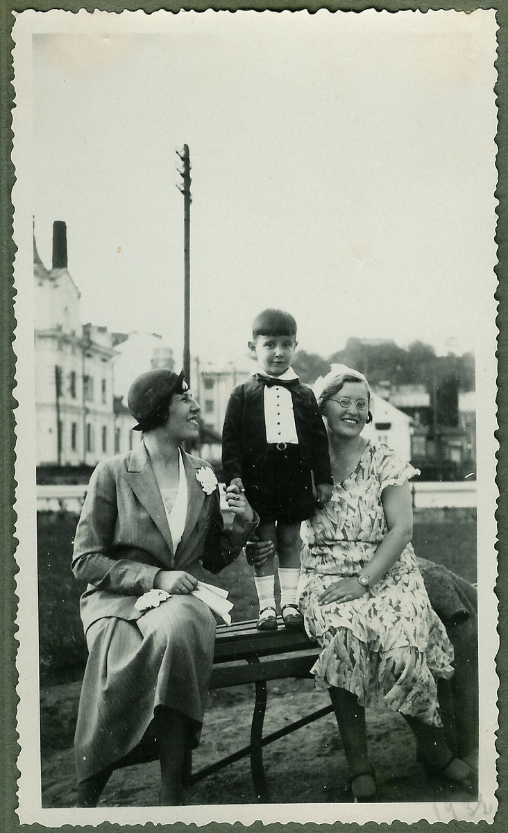 A young Lithuanian-Jewish boy dressed in formal clothes poses on a park bench between his mother and nanny near his home on Vienybes Square in Kaunas.  Pictured are Eugenia and Dmitri Kopelman, and Nadezhda Jakubovskaja.