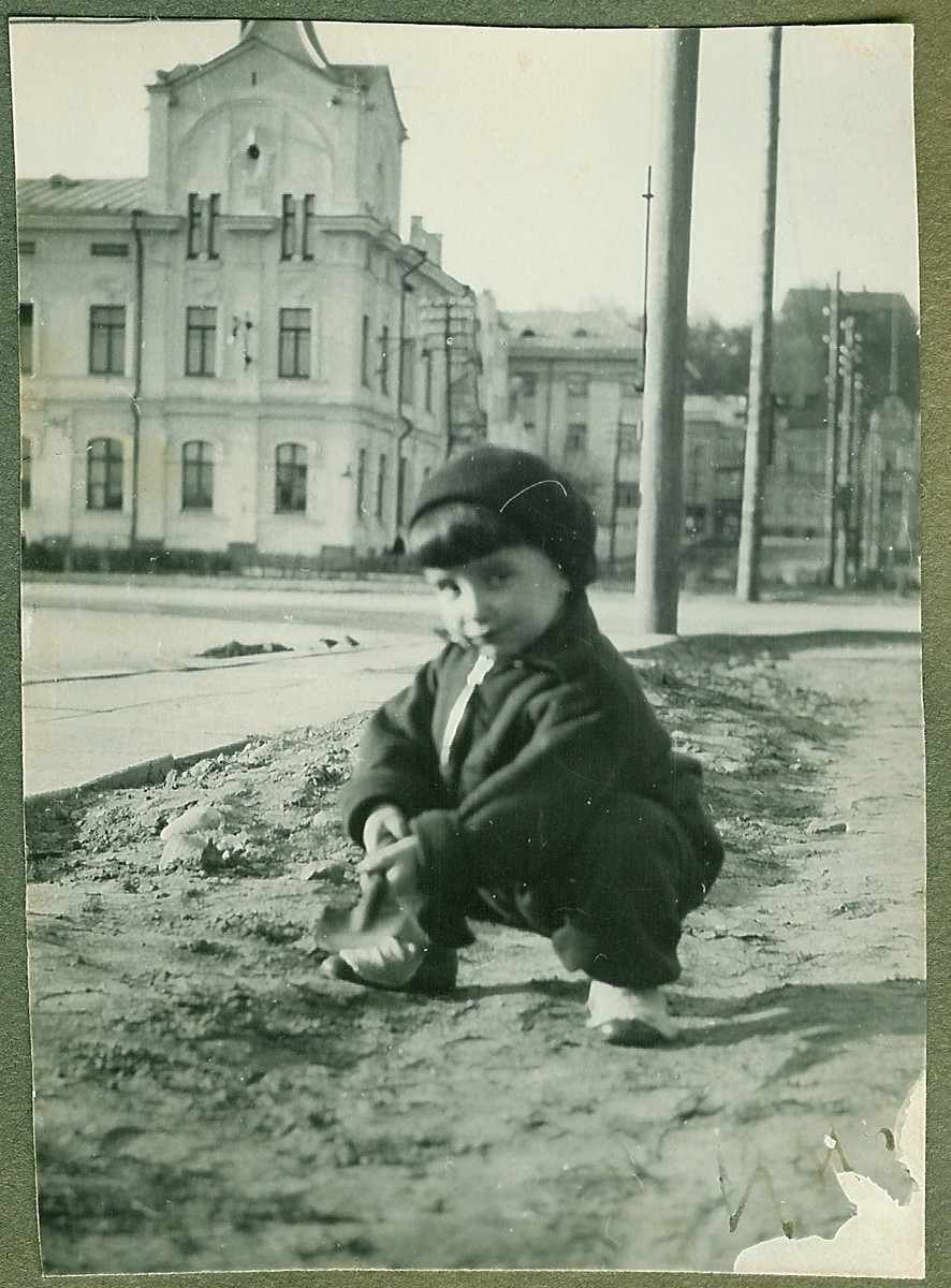 A three-year-old Lithuanian-Jewish boy poses near his home on Vienybes Square in Kaunas.  Pictured is Dmitri Kopelman.