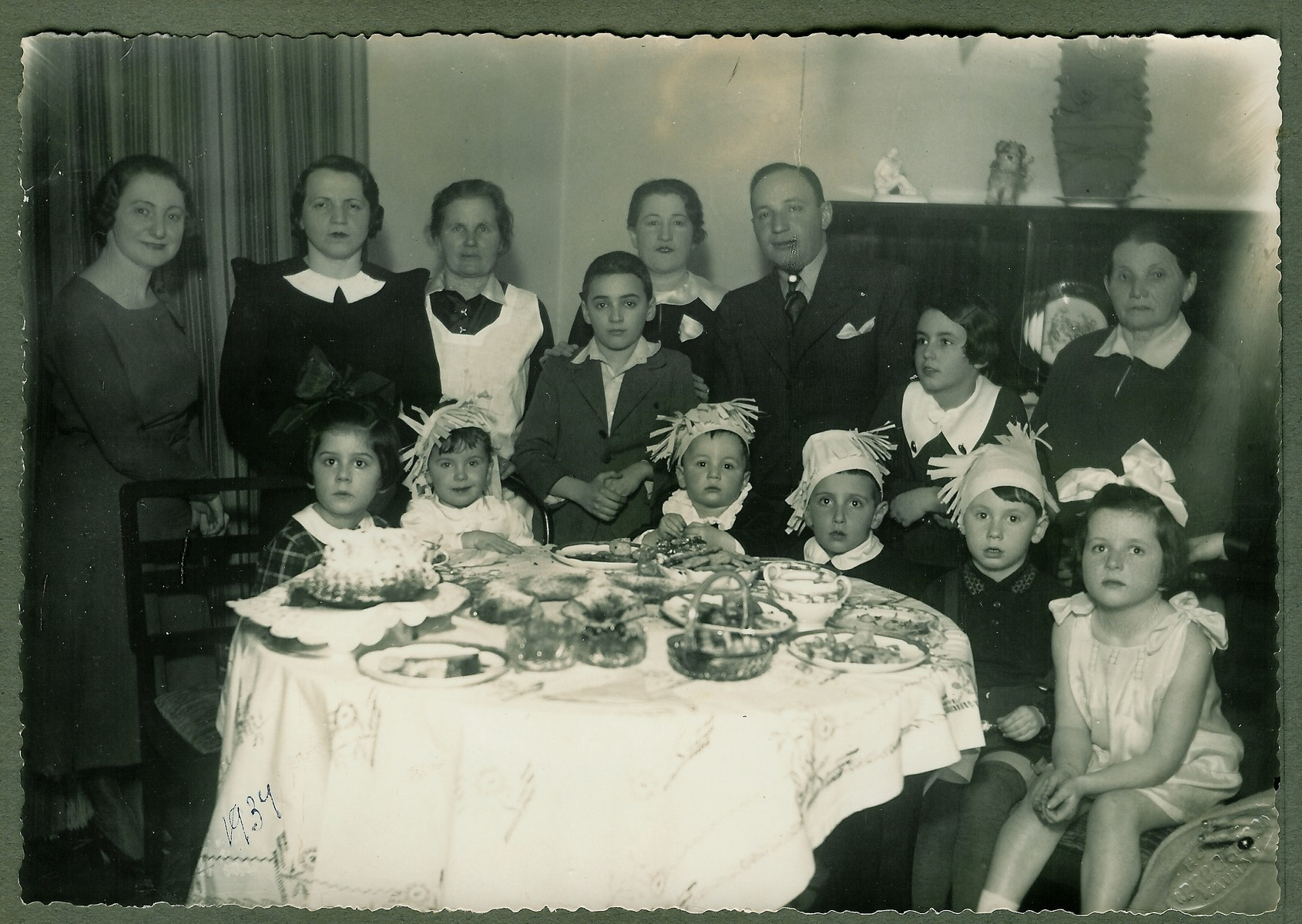 Young children accompanied by their mothers attend a birthday party.  Seated from left to right are Renata (?), Aleksandras Shtromas, Liova Shtrom, Dmitri Kopelman, Mulik Trotzky, Irena Veisaite.  Standing from left to right are unknown, Sonia Veis, nanny of Aleksandras Shtromas, Waldemar Ginsburg, Edith Shtromiene, Ovsey Shtrom, Margarita Shtromaite, and Chaya Shtromiene.