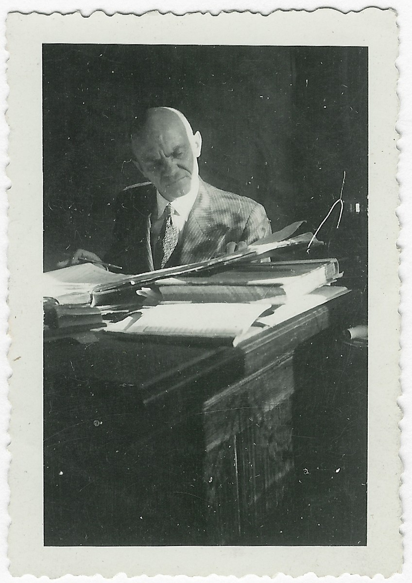Aleksandras Valaitis works at his desk in the insurance company, Lietuvos Lloydas.  Aleksandras Valaitis helped hide the Kopelman family and two other Jewish women after they fled the Kovno ghetto during its liquidation.