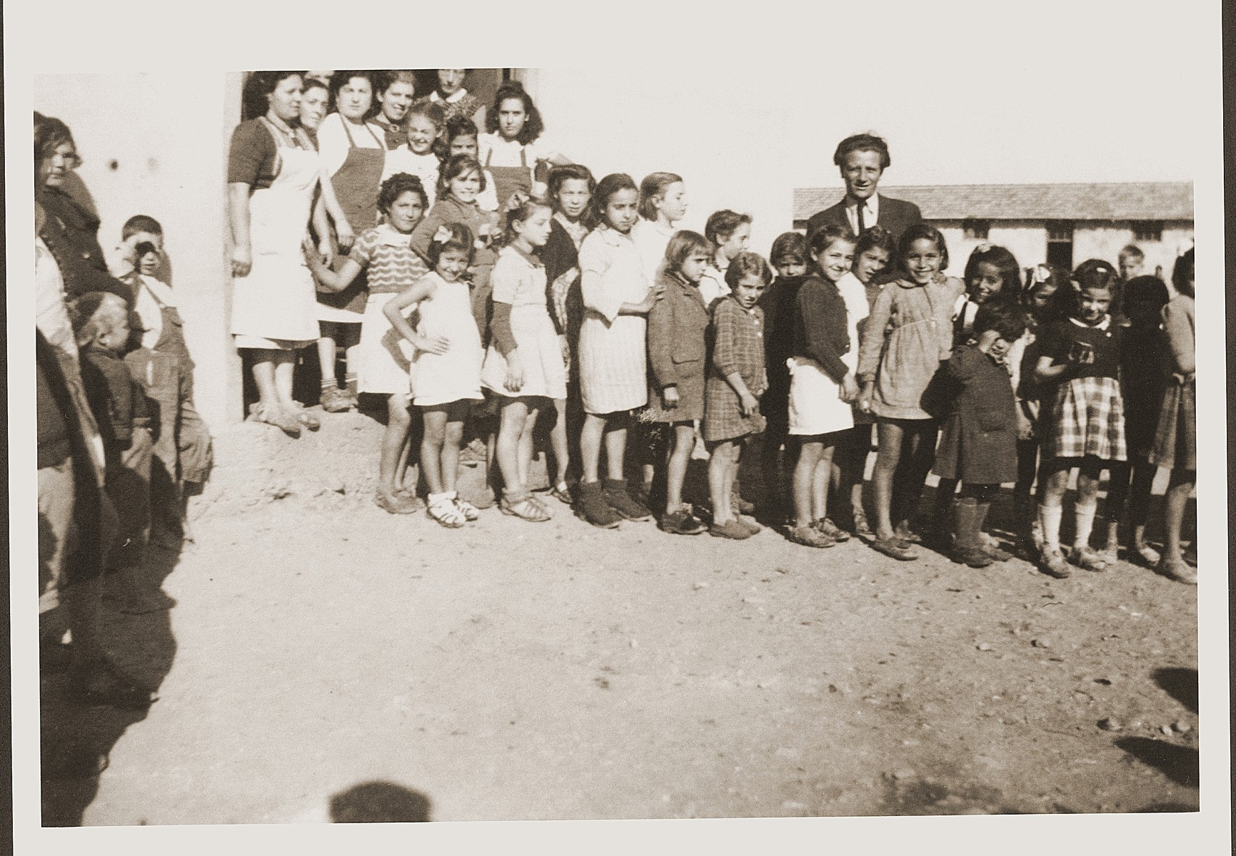 Children and asi workers pose outside the barracks of the Secours Suisse aux enfants in Rivesaltes.