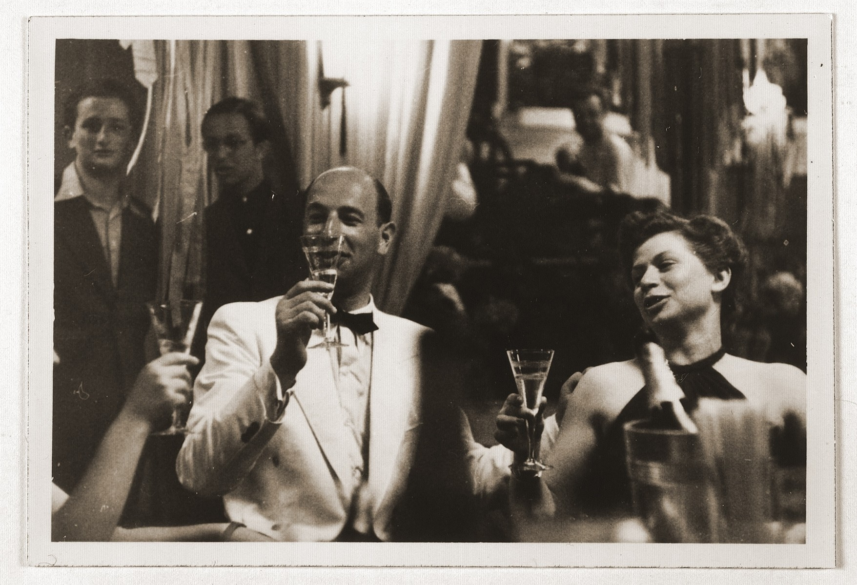 An unidentified couple in evening dress drinks champagne aboard the MS St. Louis.