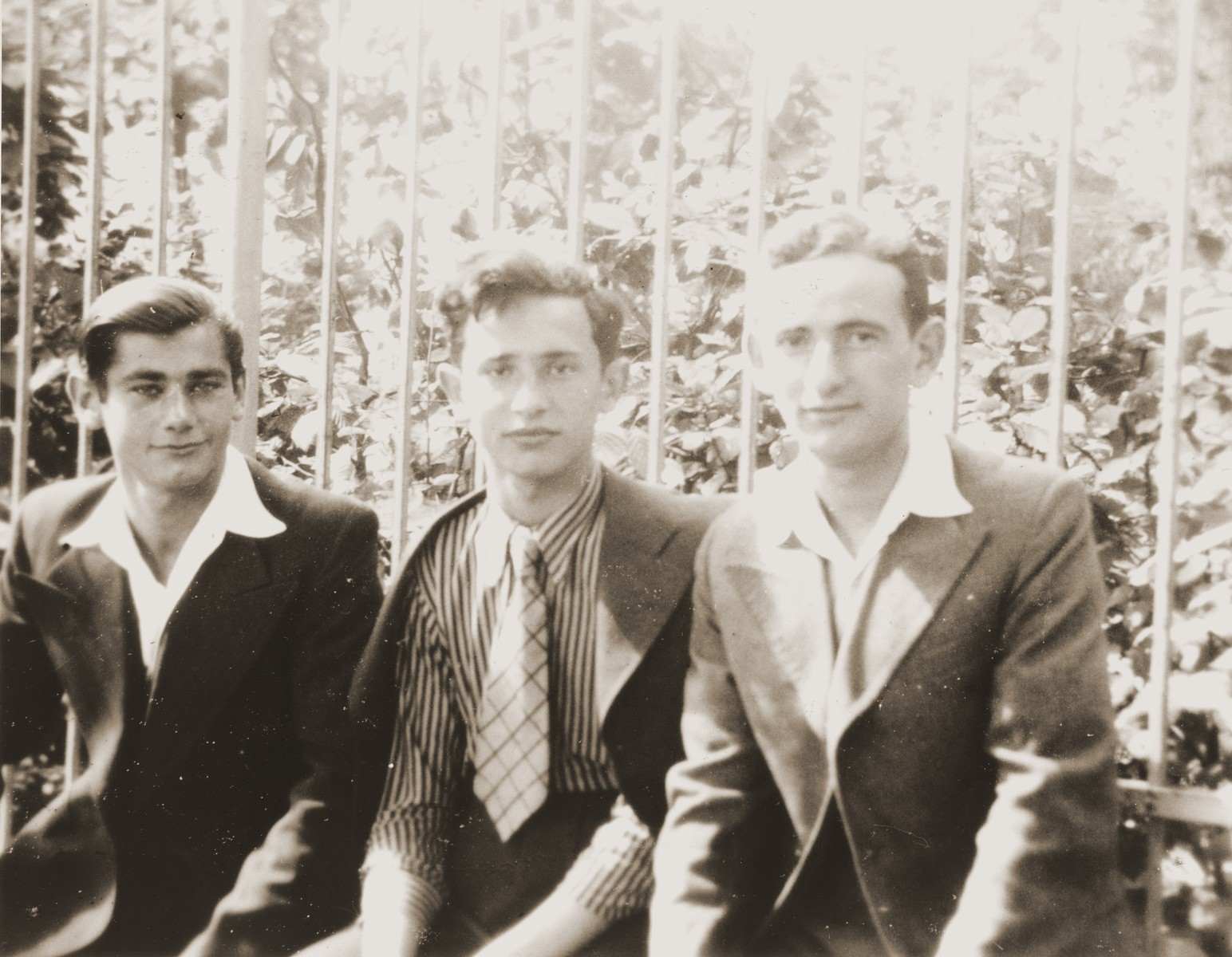 Three Jewish youth who are graduating high school together pose outside in Brody, Poland.  Pictured from left to right are: Josef Ettinger, unknown, and Henryk Lanceter.