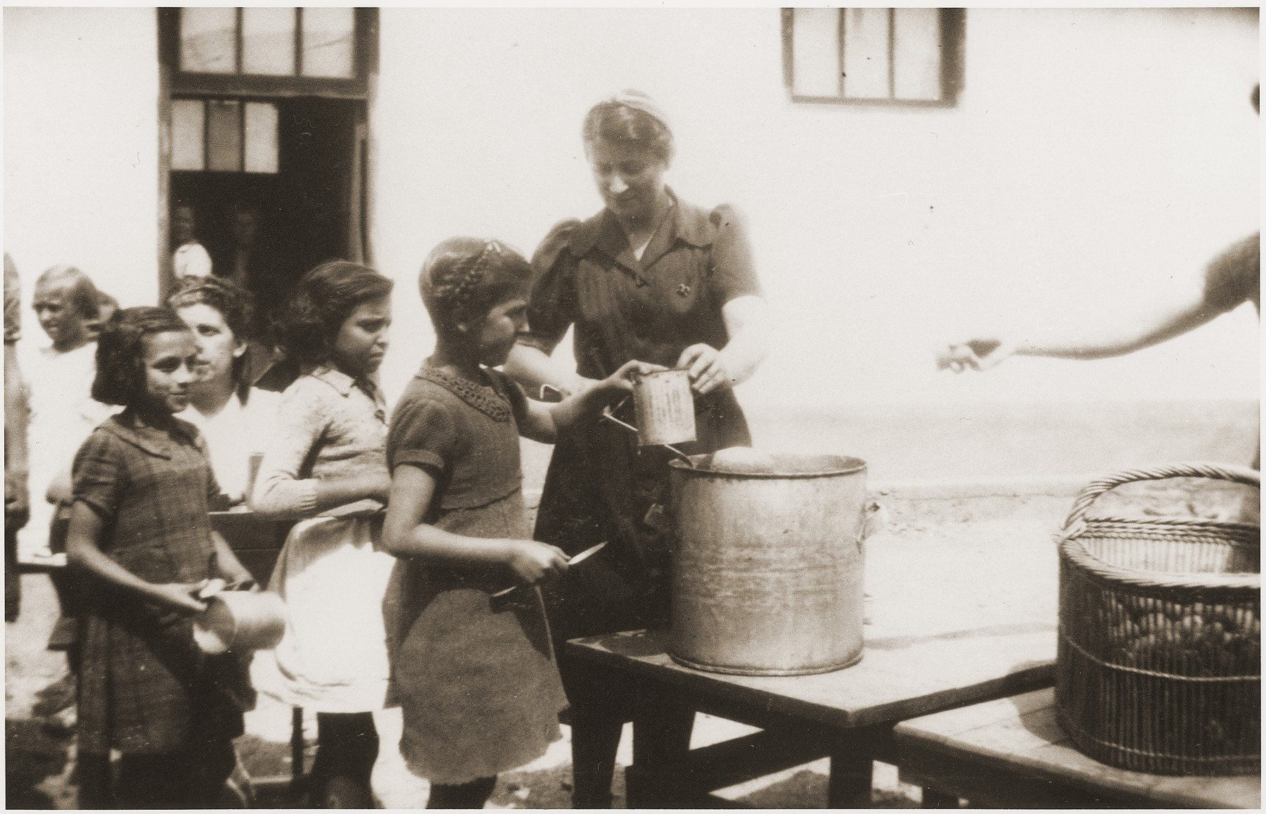 Children in the Rivesaltes transit camp receive food from Secours Suisse.