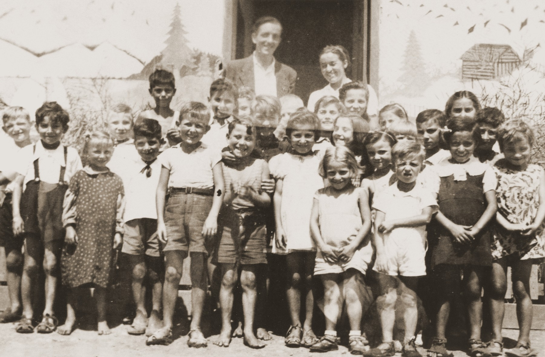 Friedel Reiter and August Bohny pose with a group of children in front of the Secours Suisse barracks in the Rivesaltes internment camp.    The building is decorated with a mural of the Swiss Alps.
