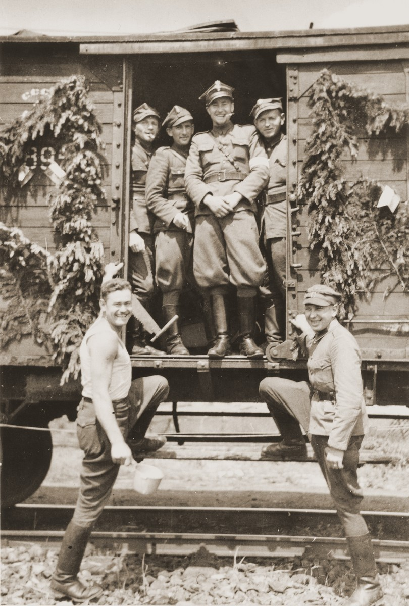 A group of Polish soldiers in the Berling Army pose in the doorway of a railcar after their arrival in Germany.  Among those pictured is the Jewish soldier Henryk Lanceter (second from the left in the railcar).