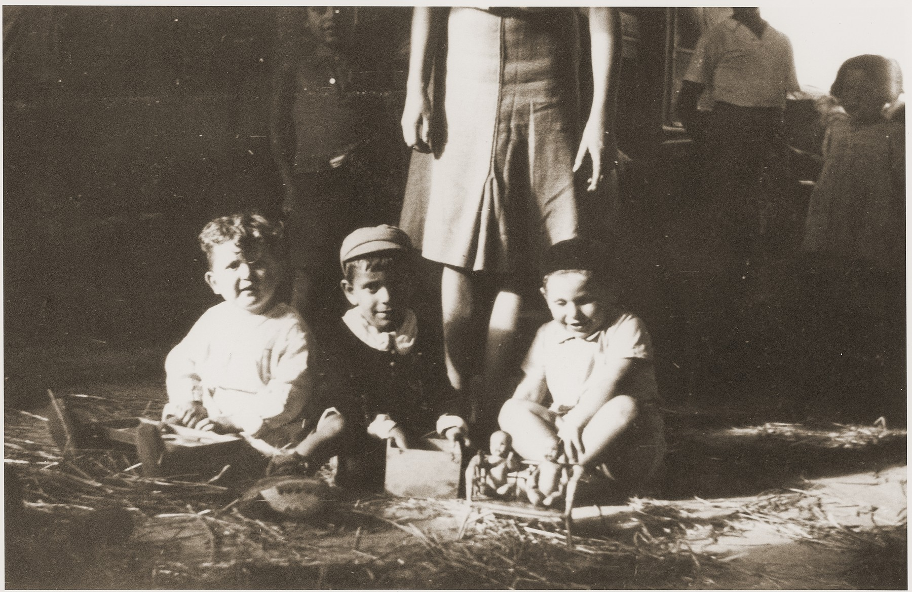 Three Jewish children in the Rivesaltes left orphaned after their parents were deported to Drancy sit on the straw strewn floor.