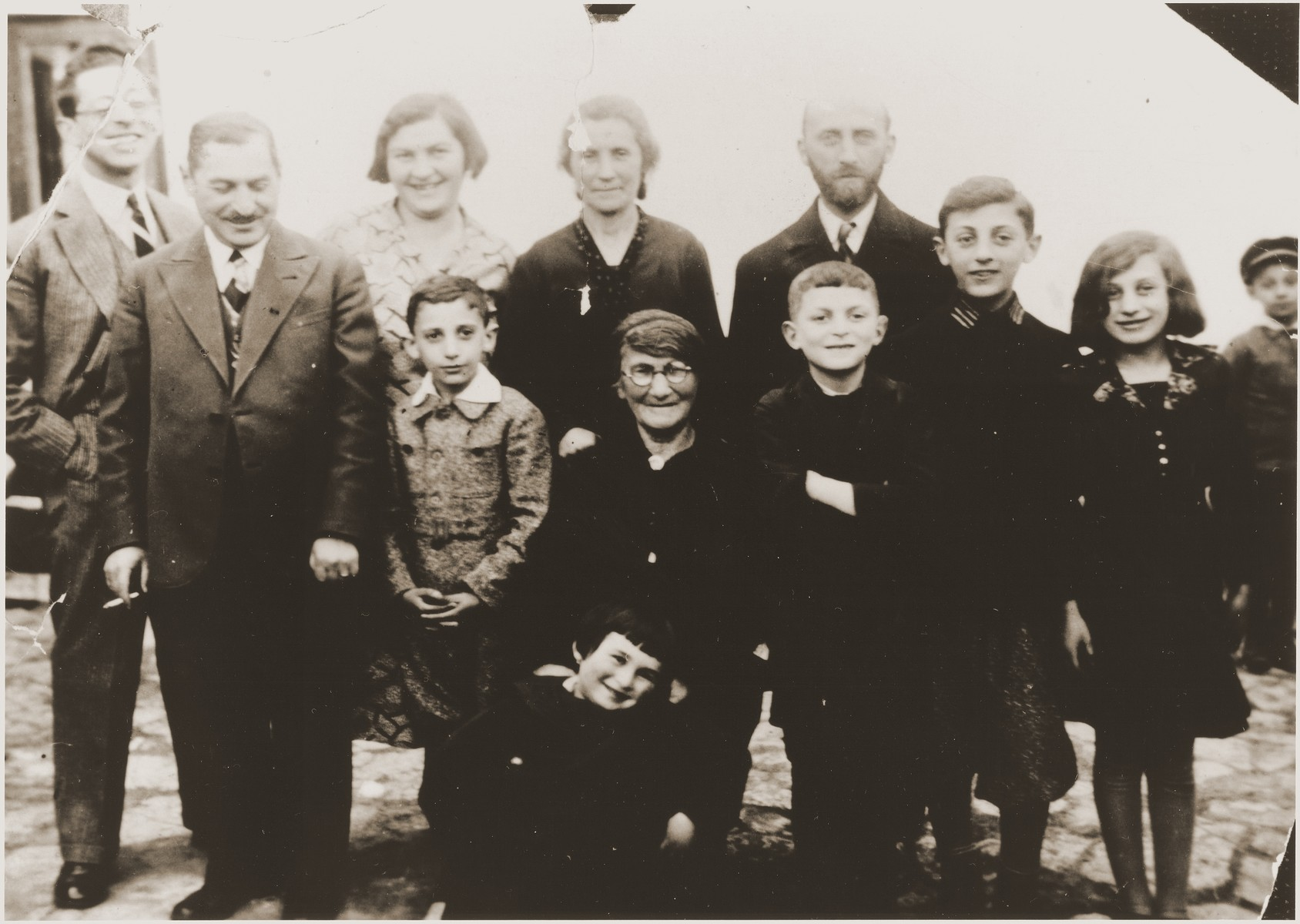 Group portrait of the extended Jewish Hochberg family in Brody, Poland.   Pictured in the back from left to right, are: Marco Chaim Lifschitz-Hochberg (the donor's uncle); Bernard Hochberg (the donor's father); Dina (Harmelin) Hochberg (the donor's mother); Malka (Hochberg) Katz (the donor's aunt); and Efraim Katz (the donor's uncle). In the middle from left to right, are: Abraham Katz (the donor's cousin); Batja (Lifschitz) Hochberg (the donor's grandmother); Sigmund Hochberg (the donor's brother); Itamar and Rachel Katz. In front is the donor, Eugenia Hochberg.