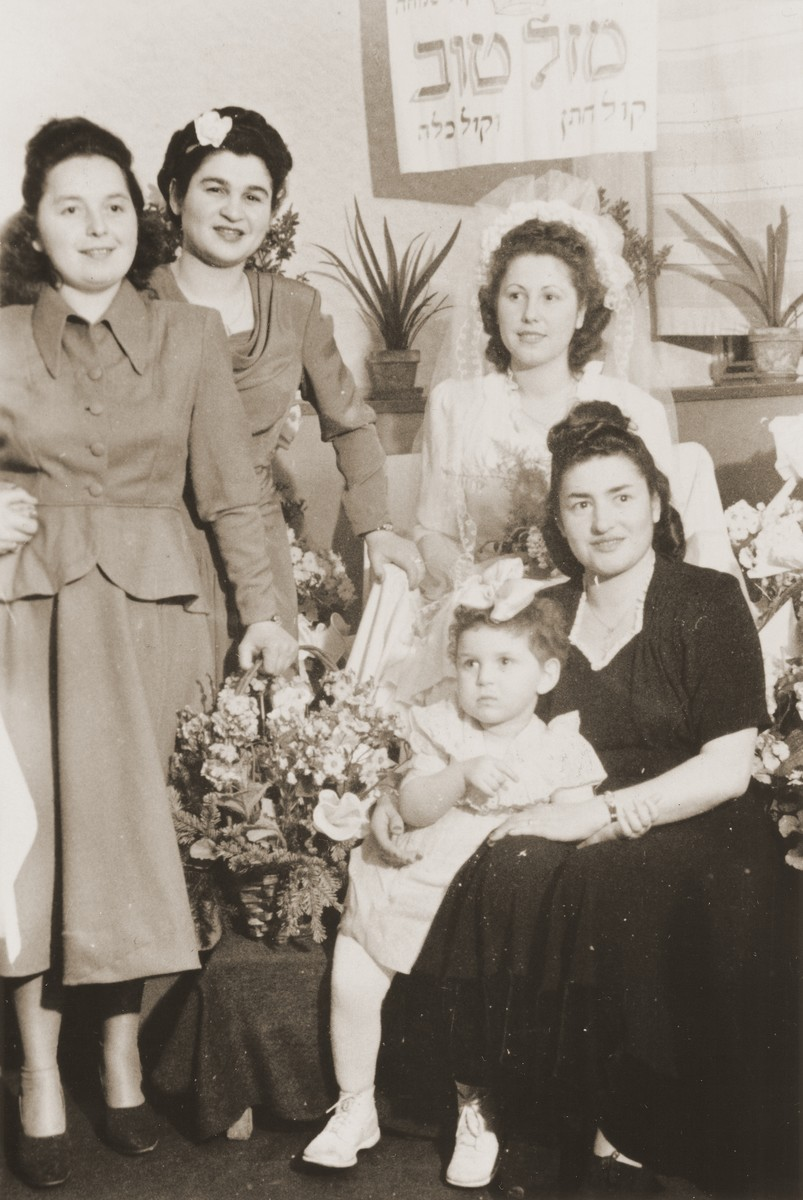 "A Jewish bride poses with a group of friends beneath a Hebrew sign at the Fuerth displaced persons camp.  The Hebrew sign reads, ""Congratulations.""  Pictured from left to right are: unknown, Ginia (Hochberg) Lanceter, Esther (Rosenberg) Blacharowicz, and Sally Rafilowicz. Standing in front is the flower girl, Dina Ella Lanceter."