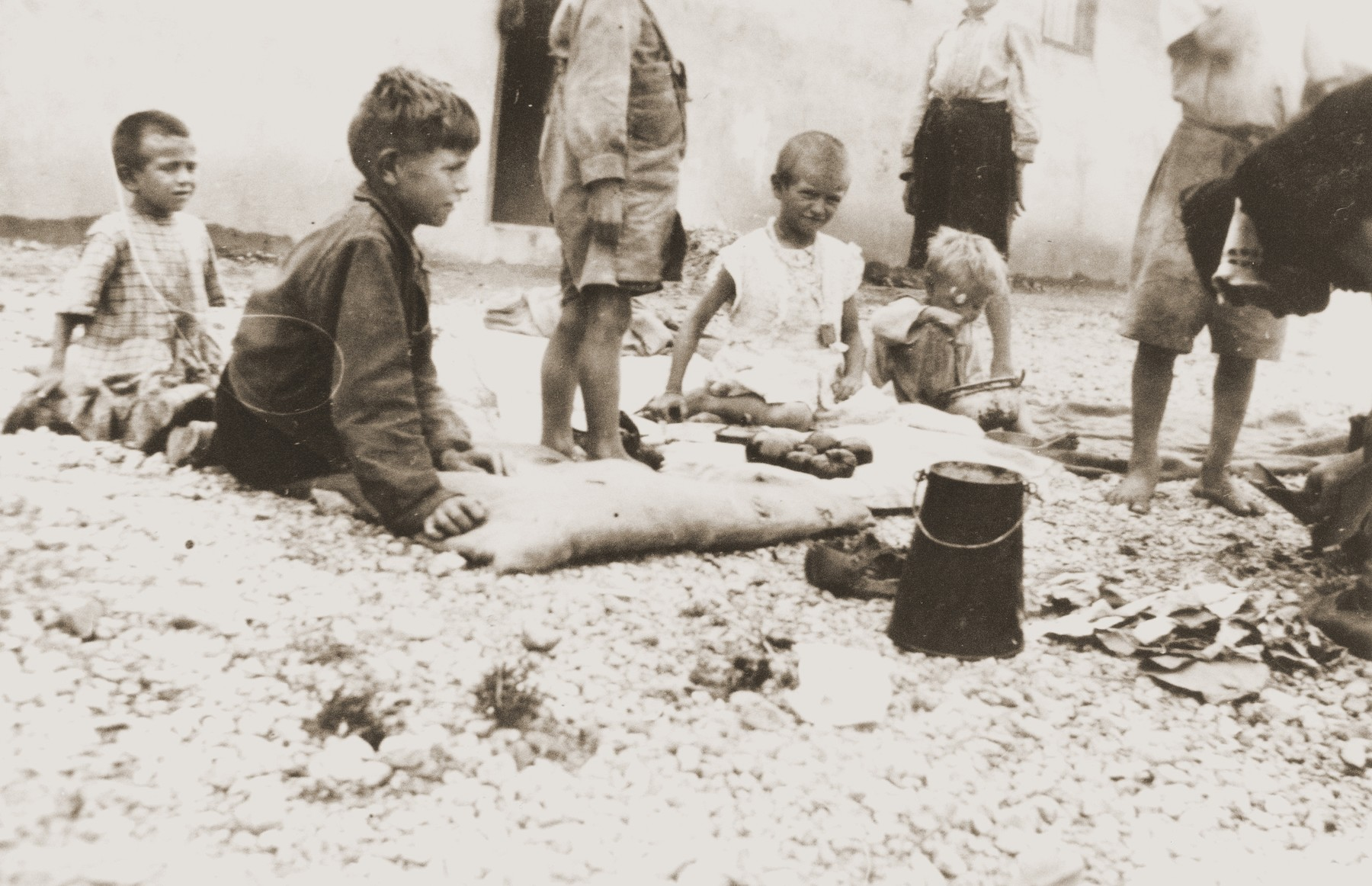 A group of children sits outside in the Rivesaltes internment camp.