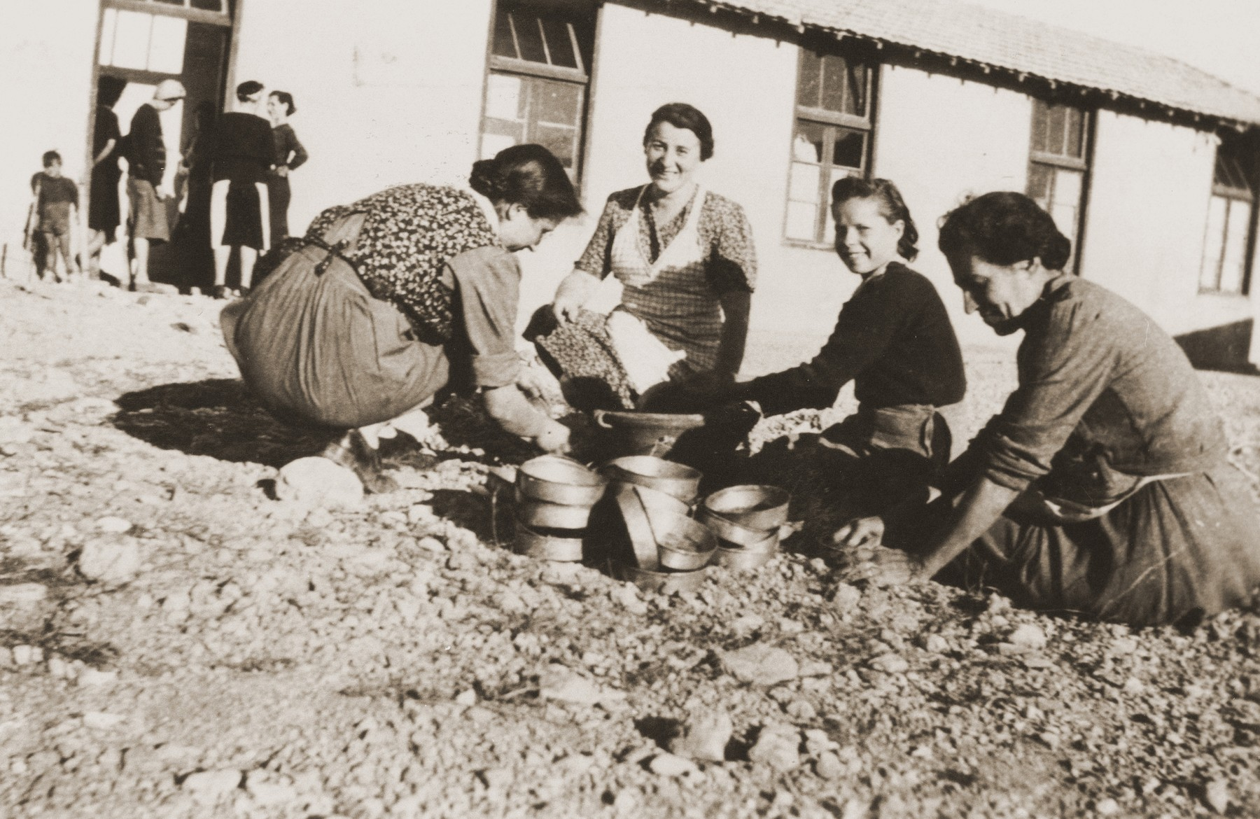 Secours Suisse aux enfants relief workers clean crockery with sand in the Rivesaltes internment camp.