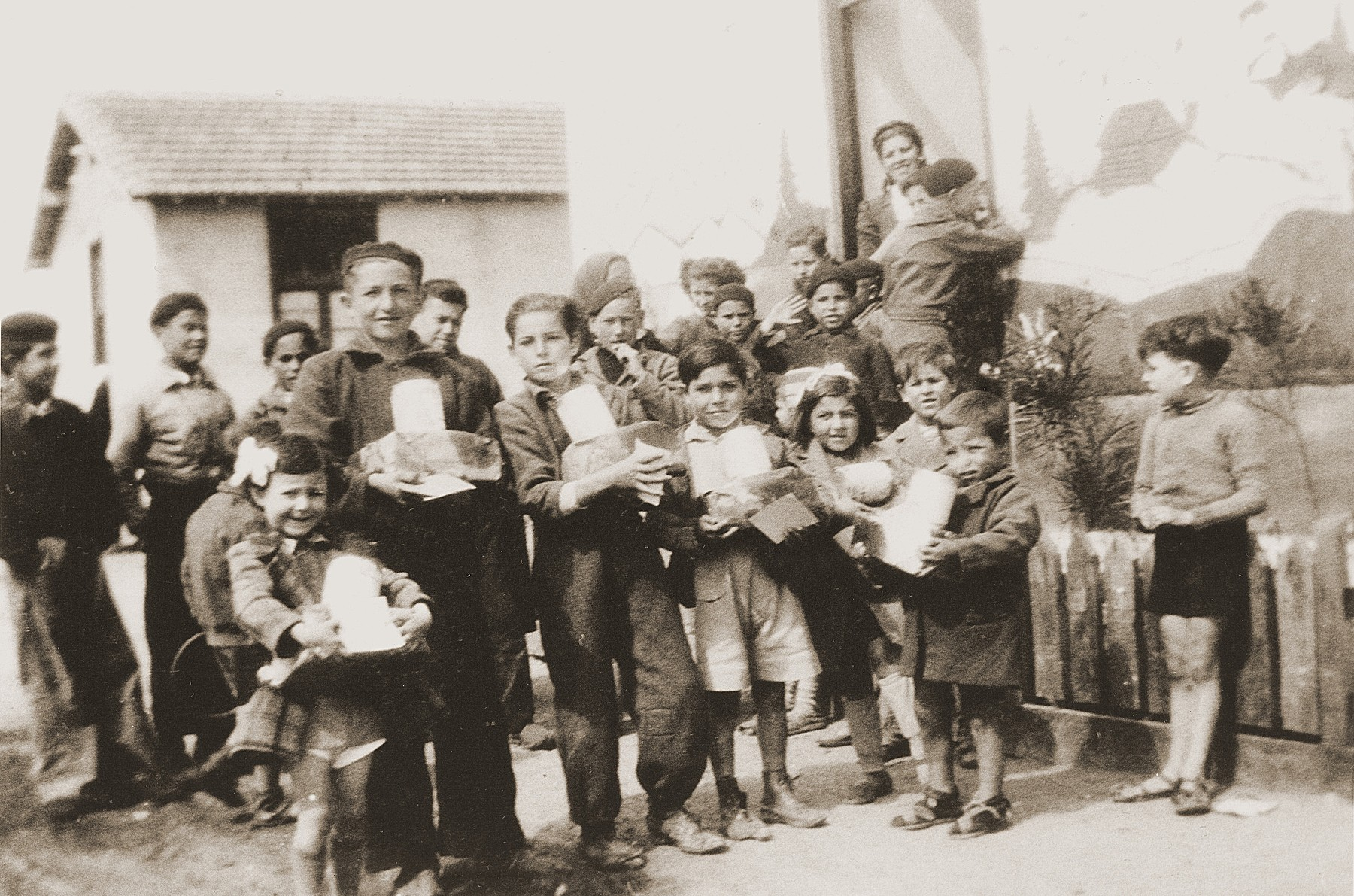 "Children display packages from their Swiss ""godparents"" in the Rivesaltes internment camp."