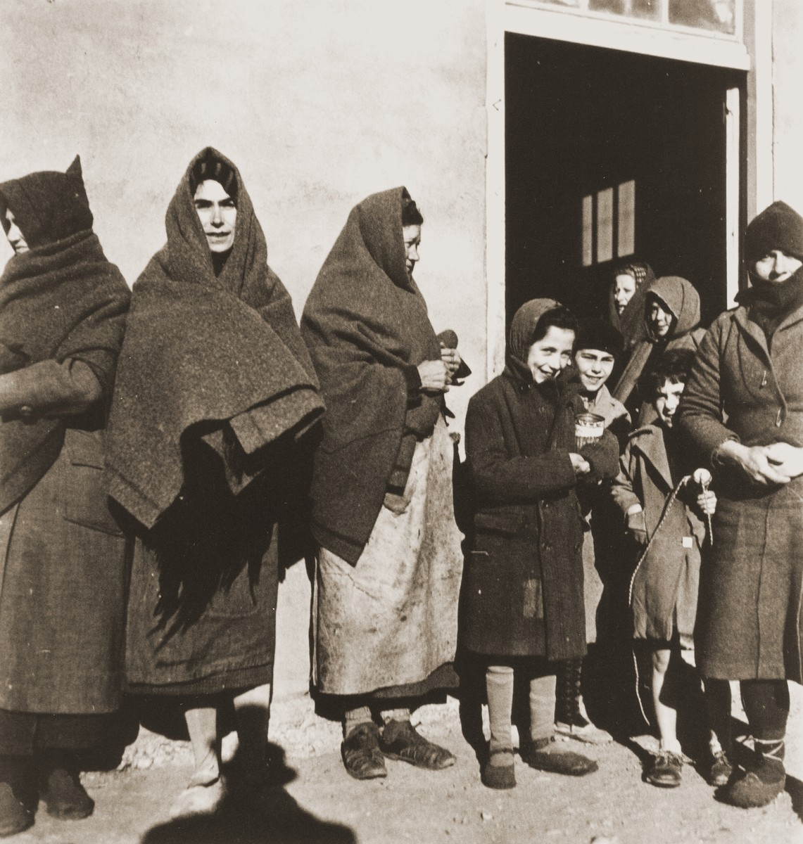 Women and children try to stay warm while waiting for food distribution.