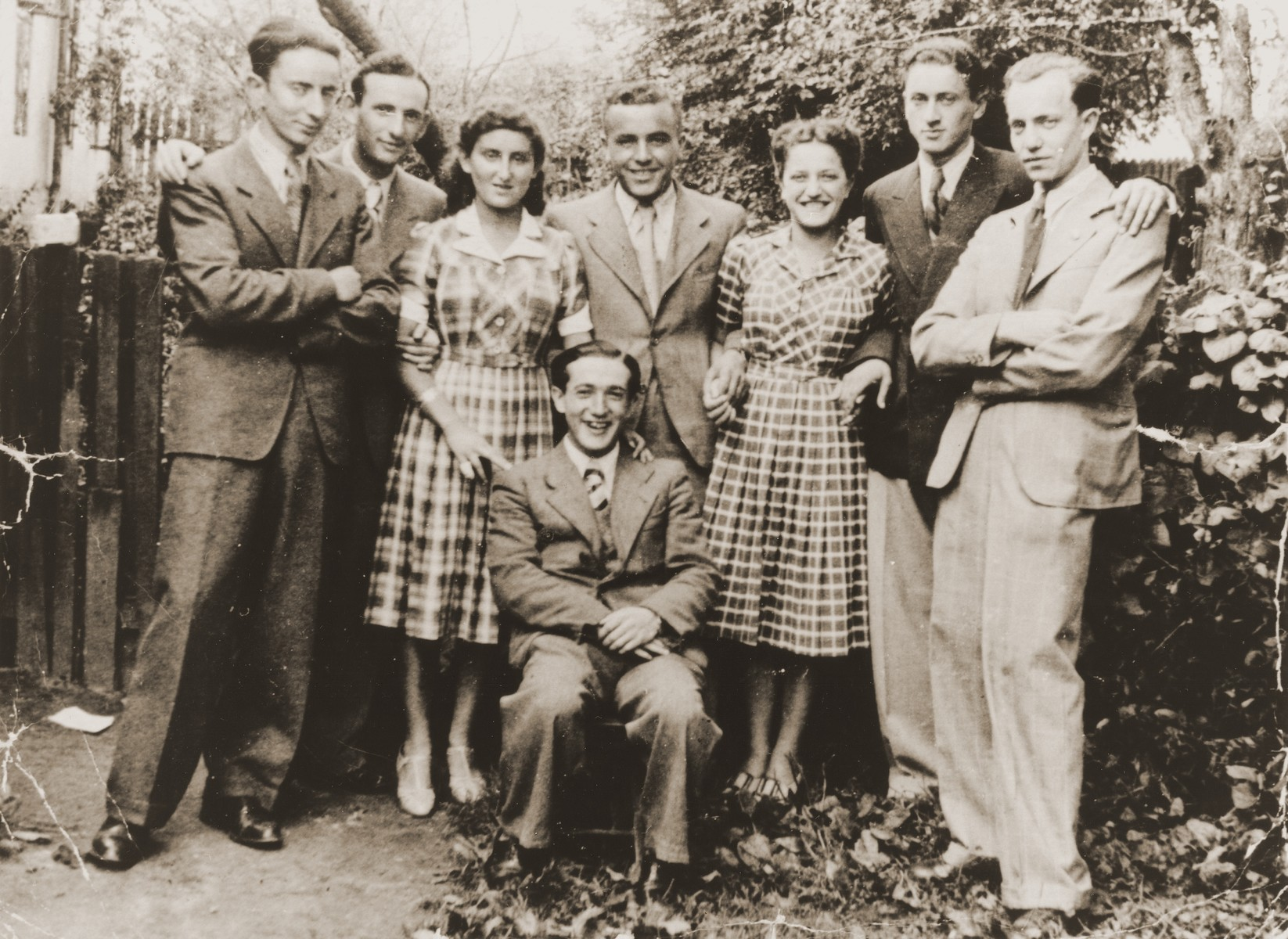 Group portrait of Jewish high school friends in Brody, Poland.  Pictured standing from left to right are: unknown, Henryk Lanceter, Ms. Buchbinder, Jacob Tomaszower, unknown, Mr. Korn, and Nathan Shapira. Seated is David Sirota.