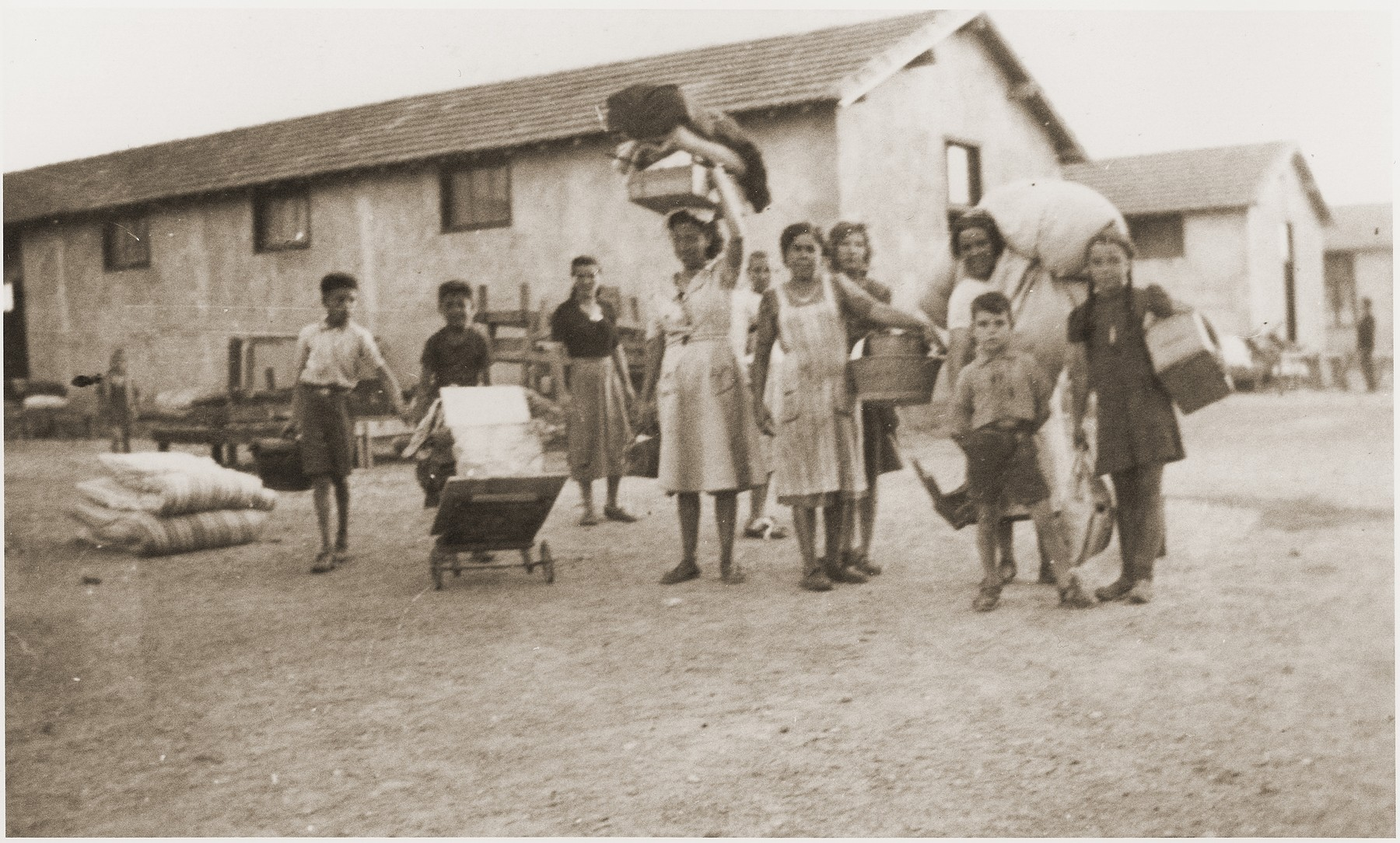 Women and children carry packages as they move to new quarters in the Rivesaltes internment camp.