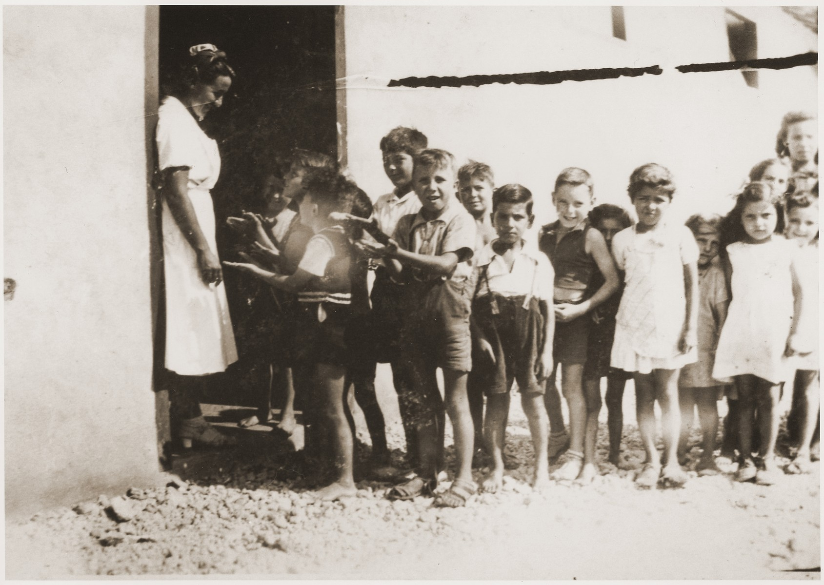 Children line up for food rations from Secours Suisse aux enfants.