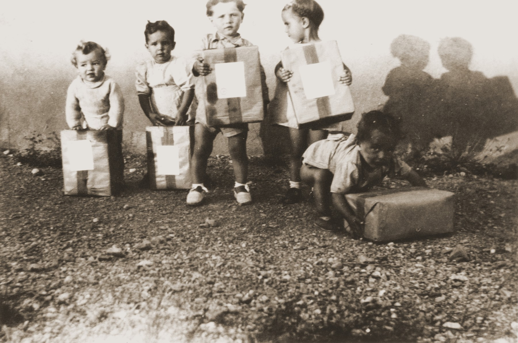 "Toddlers display packages from their Swiss ""godparents"" in the Rivesaltes internment camp."