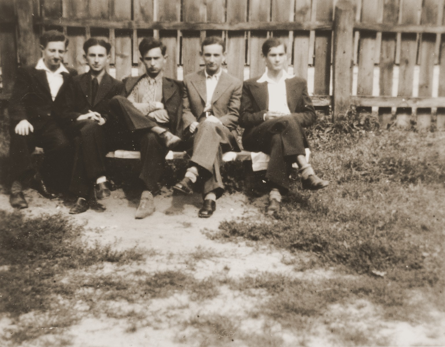 Five Jewish high school friends pose outside on a bench in front of a fence in Brody, Poland.    Among those pictured are: Joseph Ettinger (right) and Henryk Lanceter (second from the right).