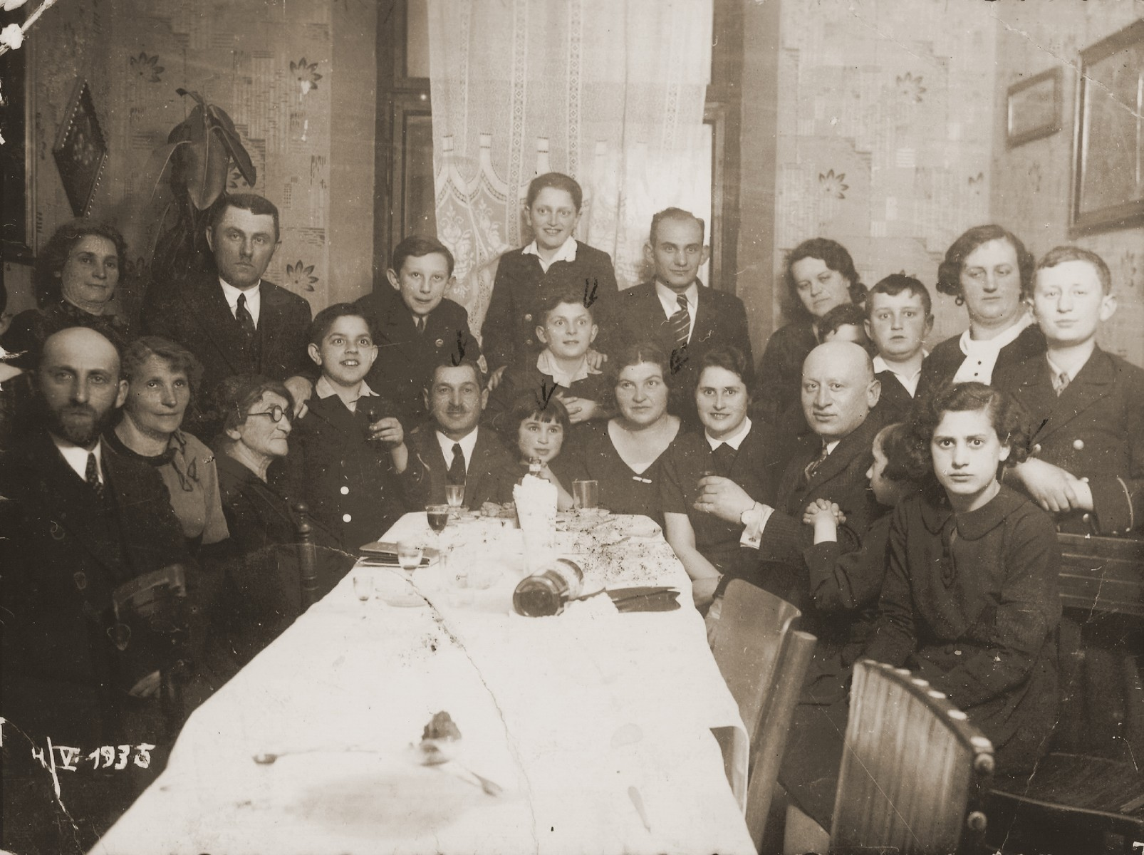 Members of the extended Hochberg family gather around a table during the celebration of the bar mitzvah of Sigmund Hochberg.    Pictured at the head of the table are Bernard and Dina Hochberg with their children Sigmund and Eugenia.  Rachel Katz is seated at the far right.  Only Eugenia and her cousin Rachel survived the war.    The donor, Eugenia Hochberg (b. November 27, 1928), is the daughter of Bernard and Diana Harmelin Hochberg of Brody, Poland.  She had one brother, Sigmund (b. 1922).  Her father earned his living as a grain shipper.  Eugenia attended a private non-religious Jewish school in Brody.  After the German invasion and the repartition of Poland in the fall of 1939, Brody came under Soviet occupation.  For two years the Hochbergs remained in their home, but were compelled to share their living quarters with other Jewish families.  No longer permitted to run his own business, Bernard was forced to take work as a night watchman.  In June 1941, following the German invasion of the Soviet Union, Brody fell under Nazi domination.  On November 27, 1941 Bernard was deported to a labor/concentration camp in Zborow, where he remained for five months until his wife could purchase his freedom and bring him home.  The Hochbergs relocated to the ghetto after its establishment in the winter of 1942.  During this period Eugenia was sent for forced labor to various sites outside the ghetto.  She also performed secretarial tasks in the offices of the Judenrat.  The family was rounded-up during the final liquidation of the Brody ghetto on May 21, 1943.  While on the deportation train to Majdanek, Eugenia's parents forced her to jump off before they reached their destination.  Eugenia was found semi-conscious by Polish peasants who stole her clothing and were about to take her to the police, when a railway worker appeared and insisted on taking her himself.  Instead of turning her in, however, he offered her temporary shelter and found clothes for her to wear.  Eugenia found her way back to Brody, where she smuggled herself into the forced labor camp.  Several weeks later she smuggled herself back out and found refuge with a Polish woman, who harbored other Jews for payment.  Eugenia narrowly escaped capture by the Gestapo during a raid of her place of refuge in February 1944.  Though she was able to find a Russian woman to take her in, Eugenia had to spend the last six weeks of the war concealed in a hole under the woman's bed.  Following her liberation in March 1944, Eugenia lived for a time in Brody and Lublin.  She married Henryk Lanceter in July 1945, and five months later left for Germany.  The couple took up residence in the Finkenschlag DP camp in Fuerth, where their daughter was born.  In the summer of 1949 the family emigrated to the United States, sailing aboard the SS General Holbrook to Boston.