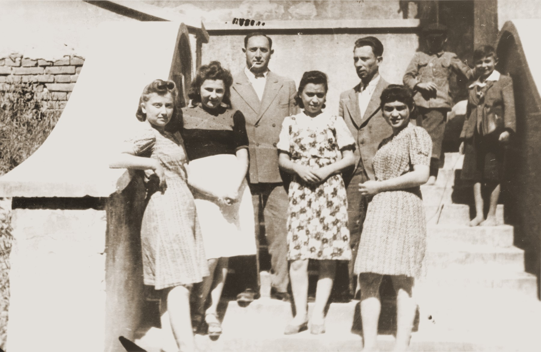 Group portrait of young Jewish DPs on the steps of a building in Lublin.  Pictured from left to right are: Rosa Lerner (Friedrich), Fryda Israelovitz (Bukar), unknown, Ms. Metches, Munio Kaczer (Kaiser), and Eugenia (Hochberg) Lanceter.