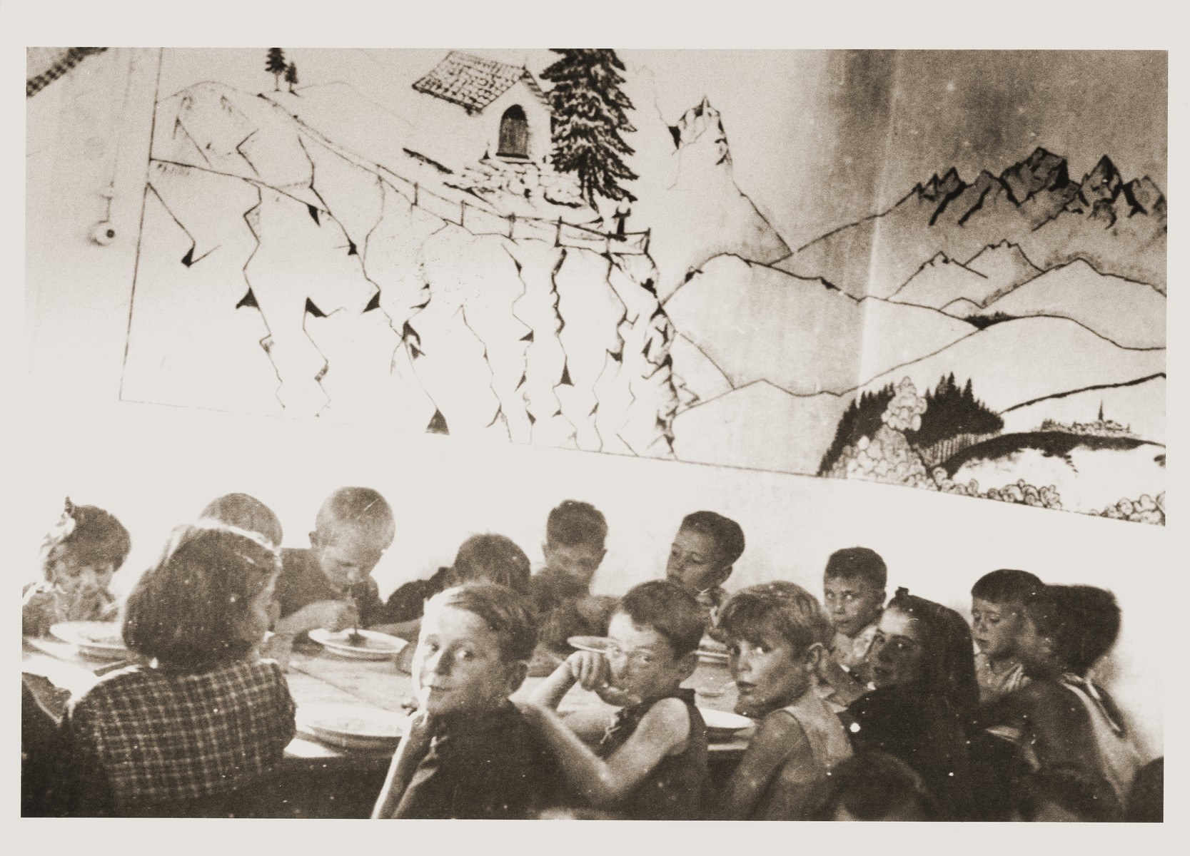Children eat a meal in the Secours Suisse dining room.  A mural of the Swiss Alps is on the wall.