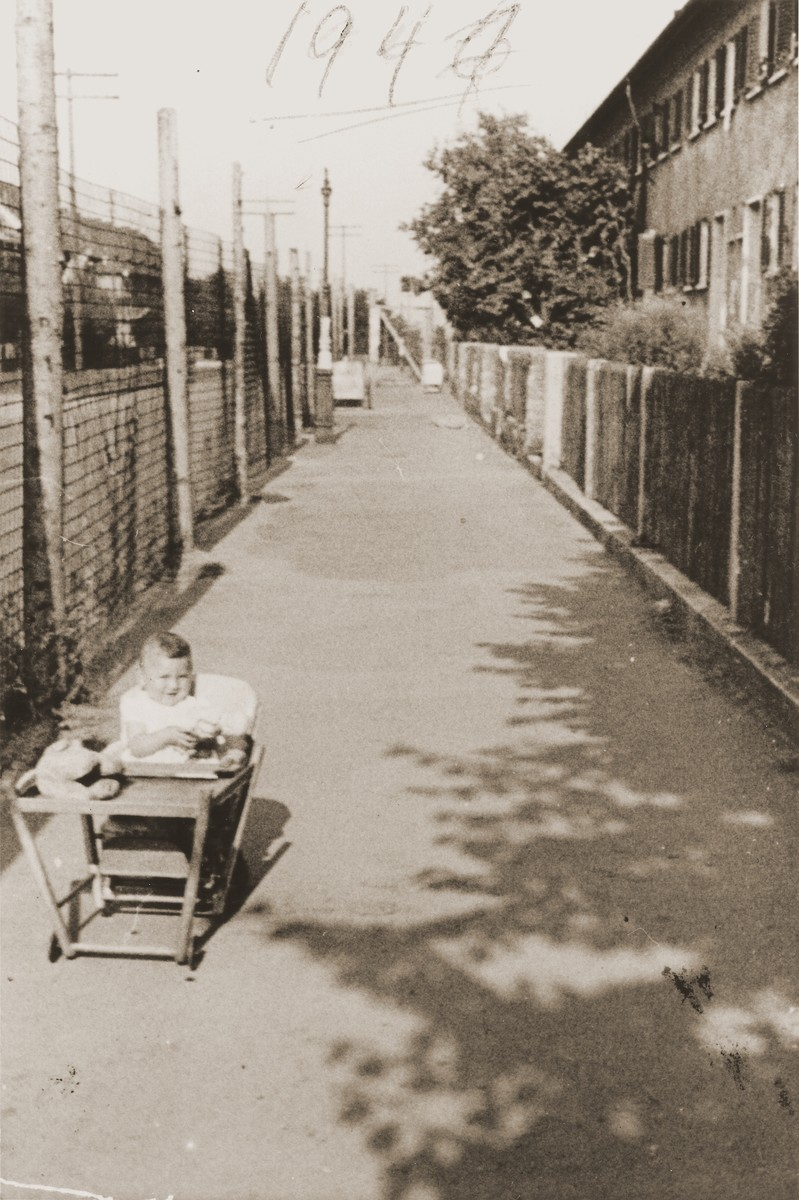 A Jewish baby sits in an infant's seat on a lane in the Finkenschlag displaced persons camp in Fuerth, Germany.  Pictured is Dina Lanceter.