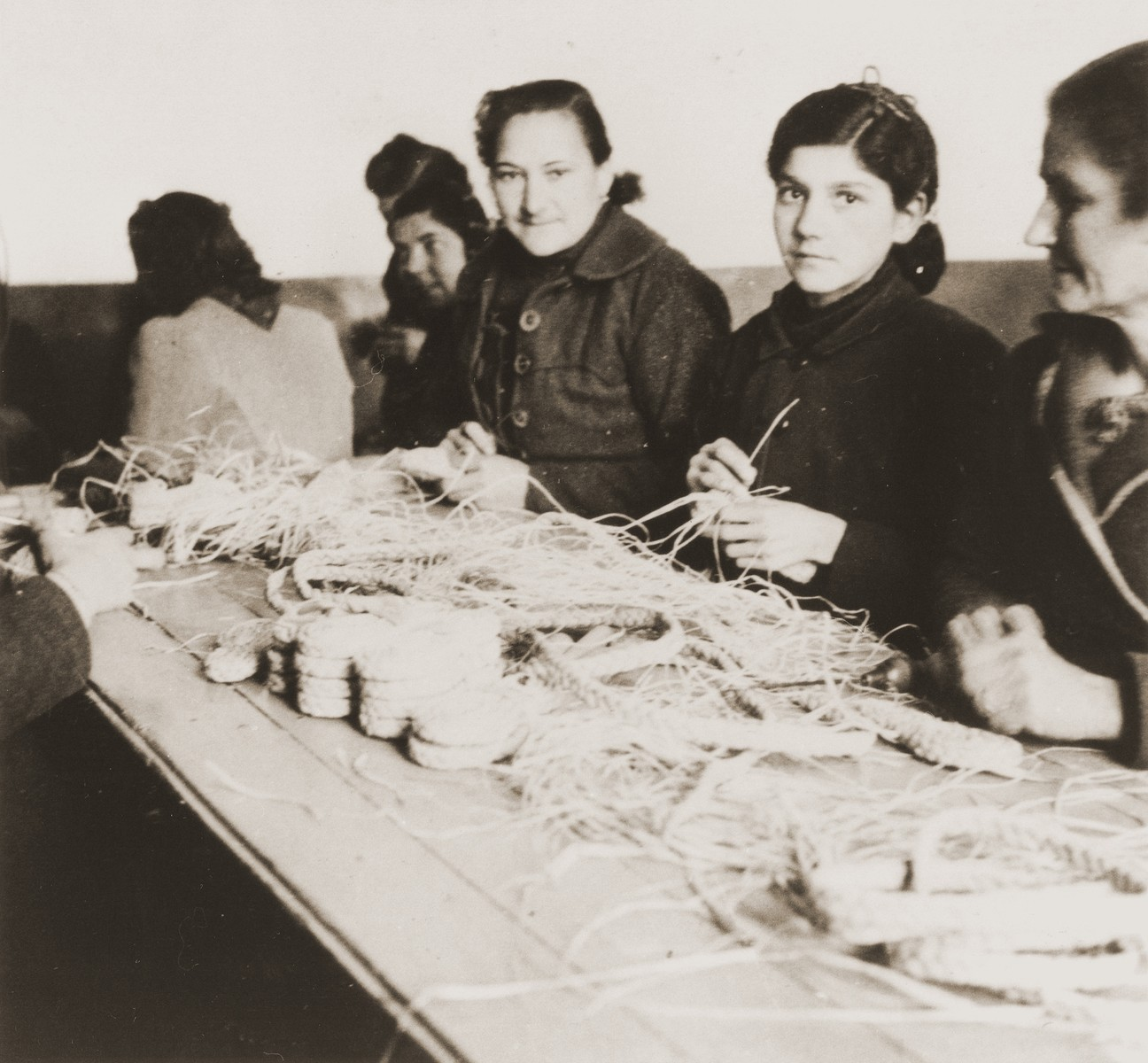 Female internees braid raffia in a workshop organized by the Secours Suisse aux Enfants.