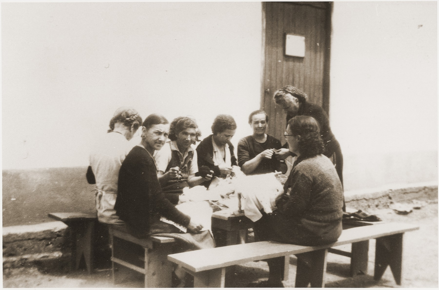 A group of female prisoners sits and sews outside one of the barracks at the Rivesaltes internment camp.