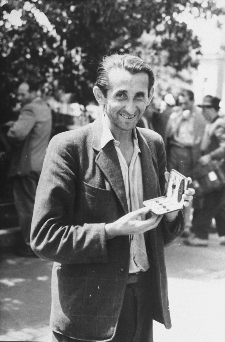 Close-up of a man holding a sewing kit in the Zeilsheim displaced persons' camp.