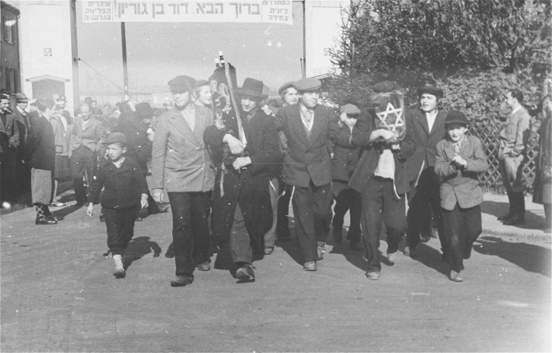 Yeshiva students march with Torah scrolls along a street in the Zeilsheim displaced persons camp, on their way to greet David Ben-Gurion during his official visit to the camp.