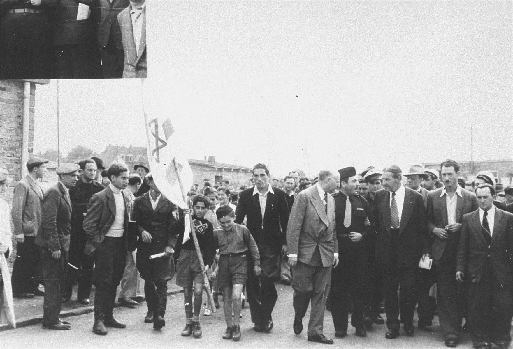 Rabbi Stephen Wise tours the Zeilsheim displaced persons camp.    Photographer Ephraim Meyer Robinson stand next to Wise on the right.